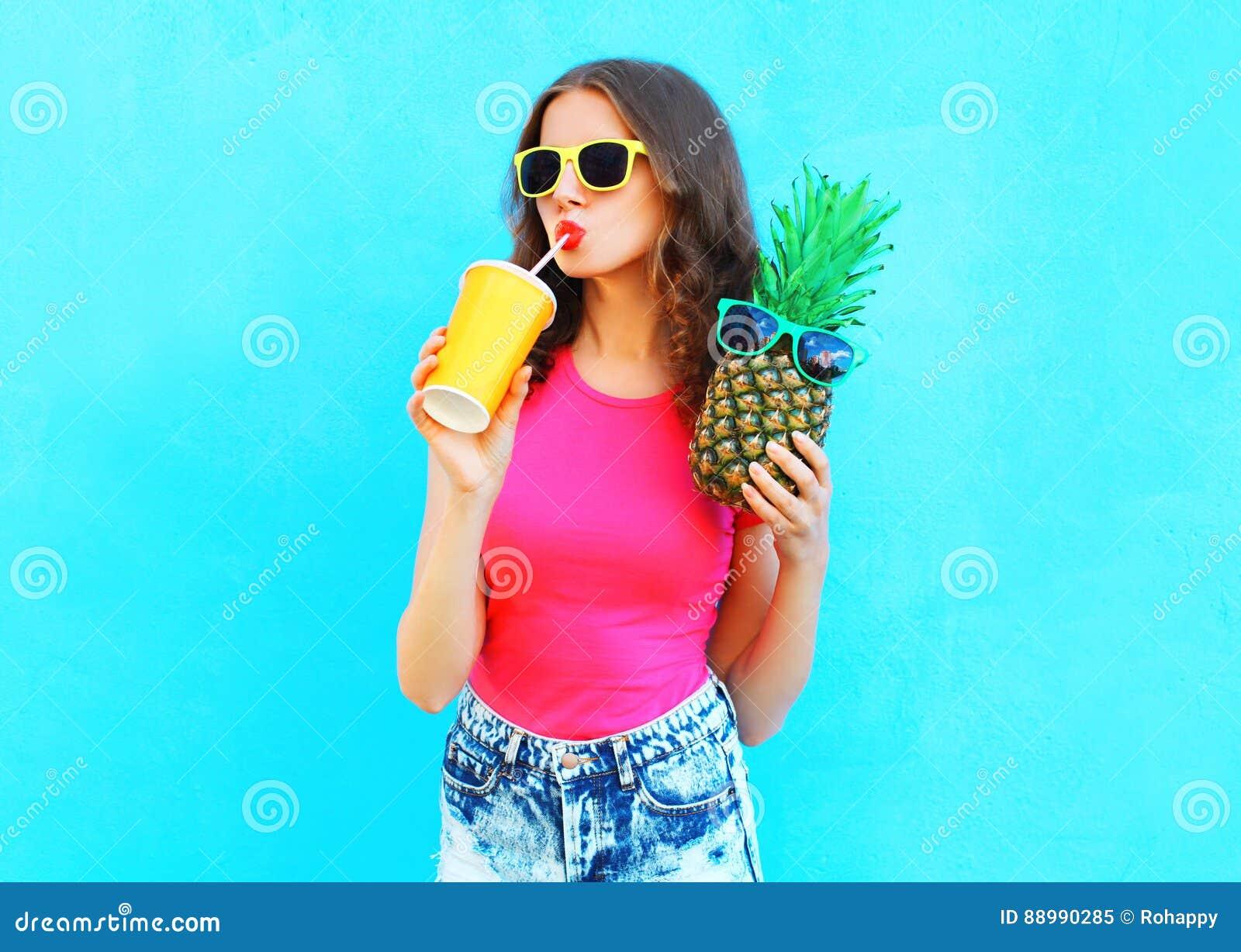 Koele meisje van het manierportret het vrij met ananas het drinken sap van kop over kleurrijk