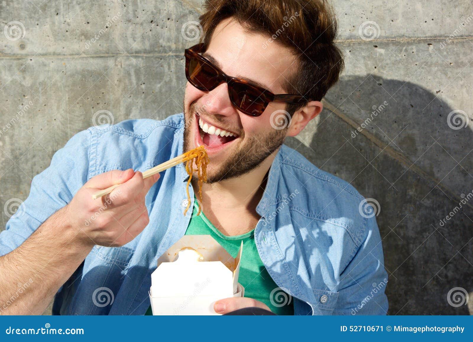 Koele mens die Chinese meeneem met eetstokjes eten