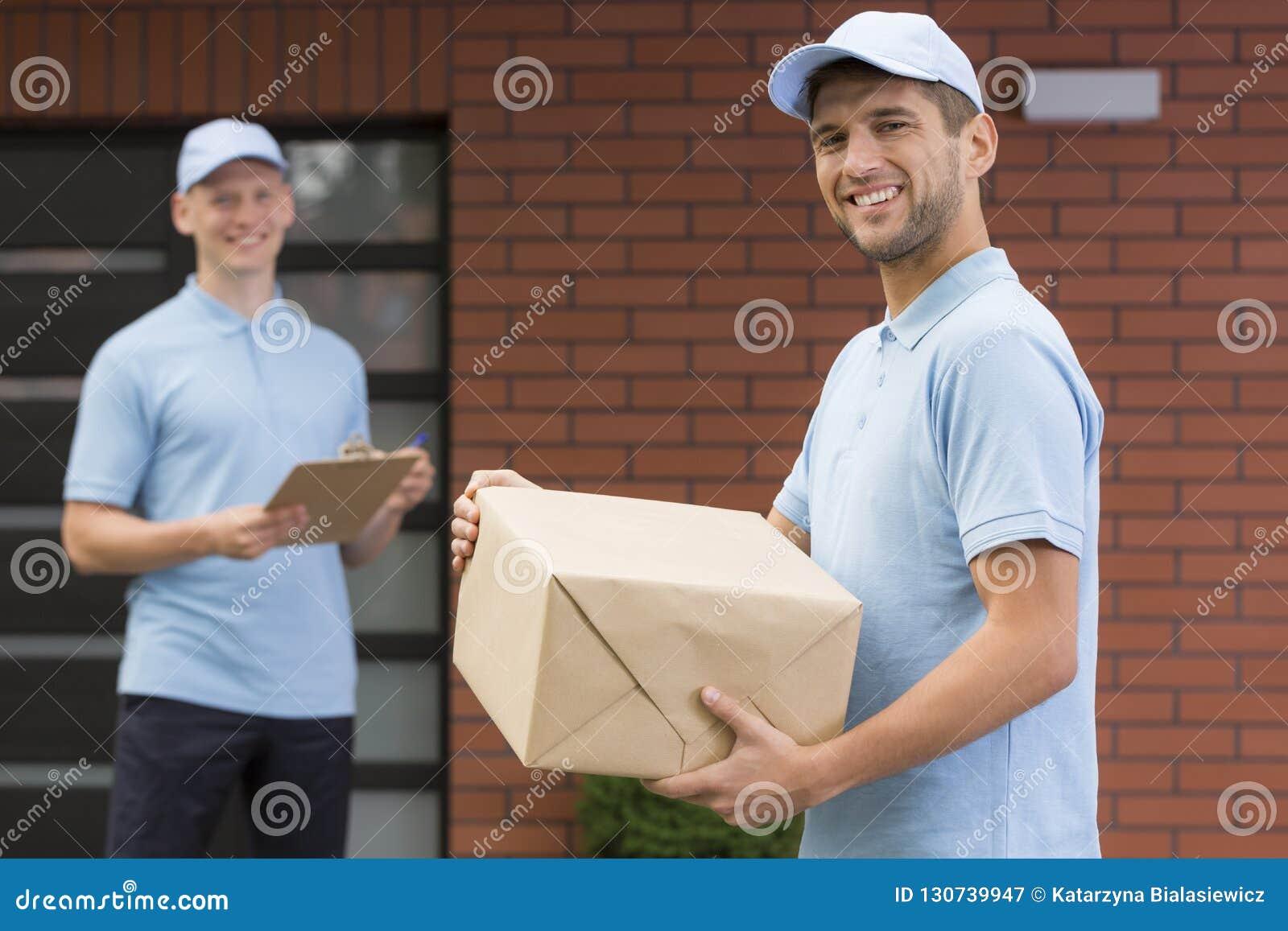 Koerier in blauwe eenvormige holding een pakket