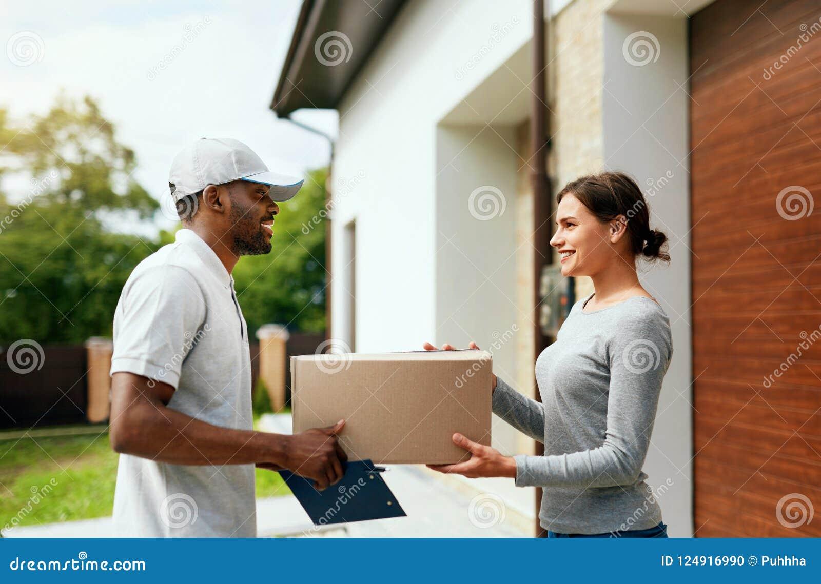 Koerier Delivery Man die Pakket thuis leveren aan Vrouw
