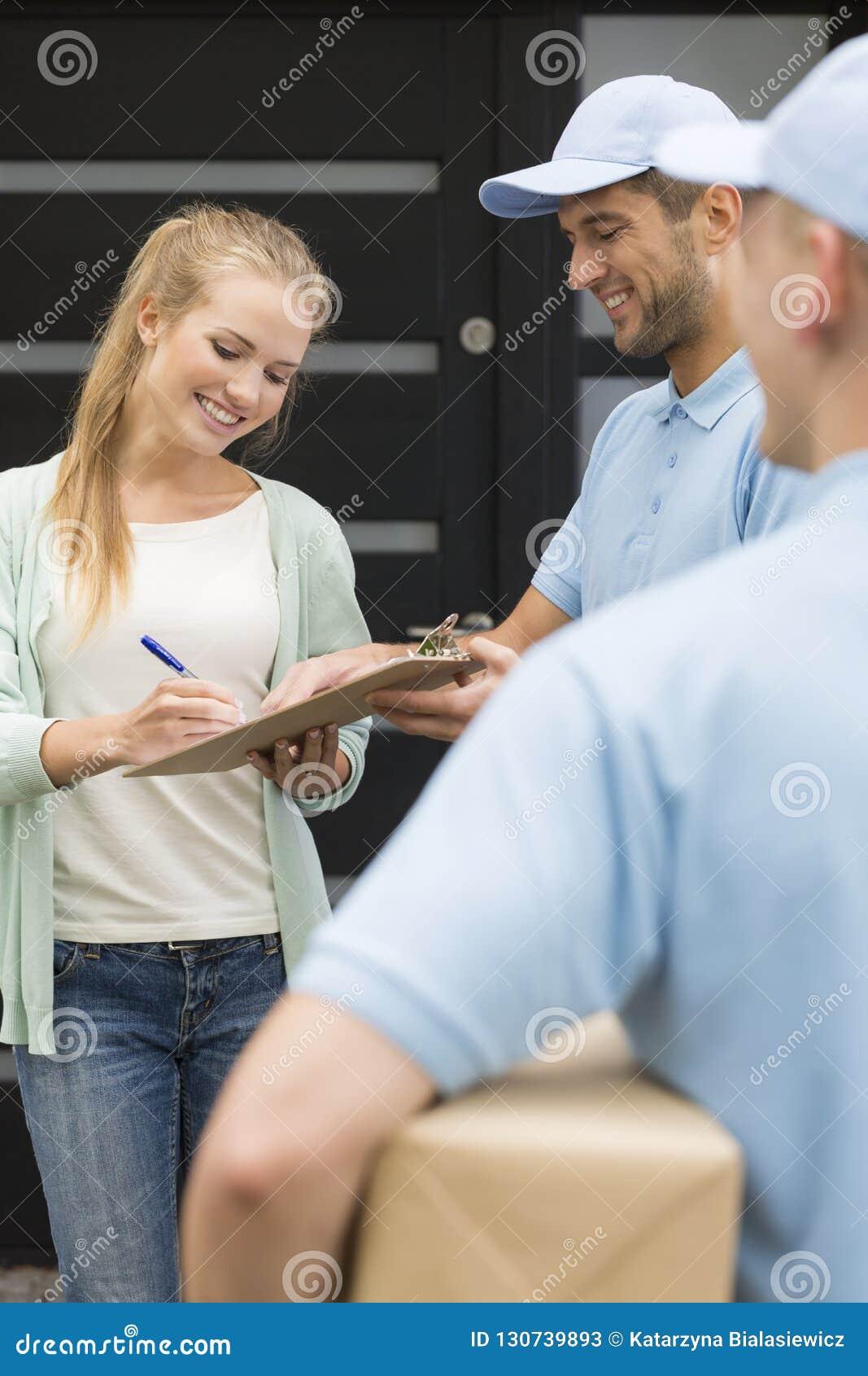 Koeriers en glimlachende klant die ontvangstbewijs van pakketlevering ondertekenen