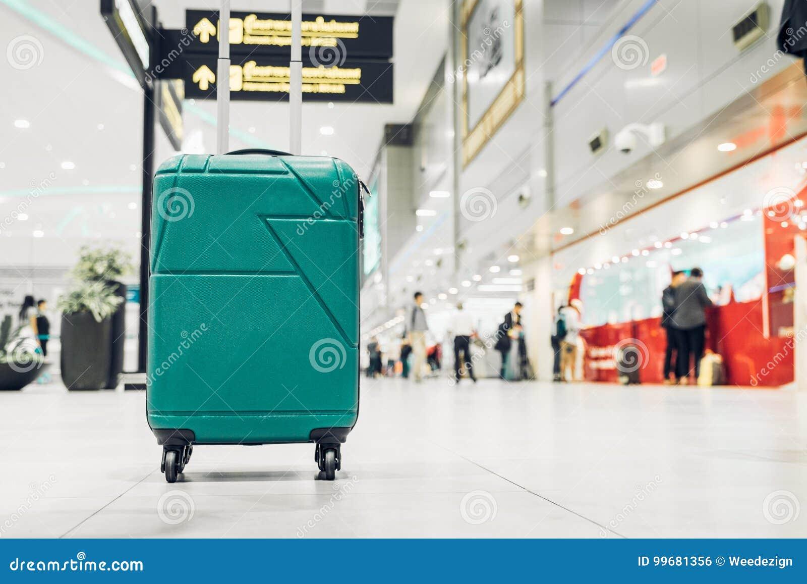Koffer im Flughafenabfahrtanschluß mit den Reisendleuten wal