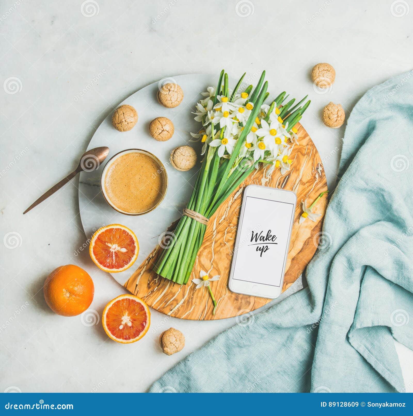 Koffie, koekjes, sinaasappelen, bloemen, mobiele telefoon met woord omhoog Kielzog