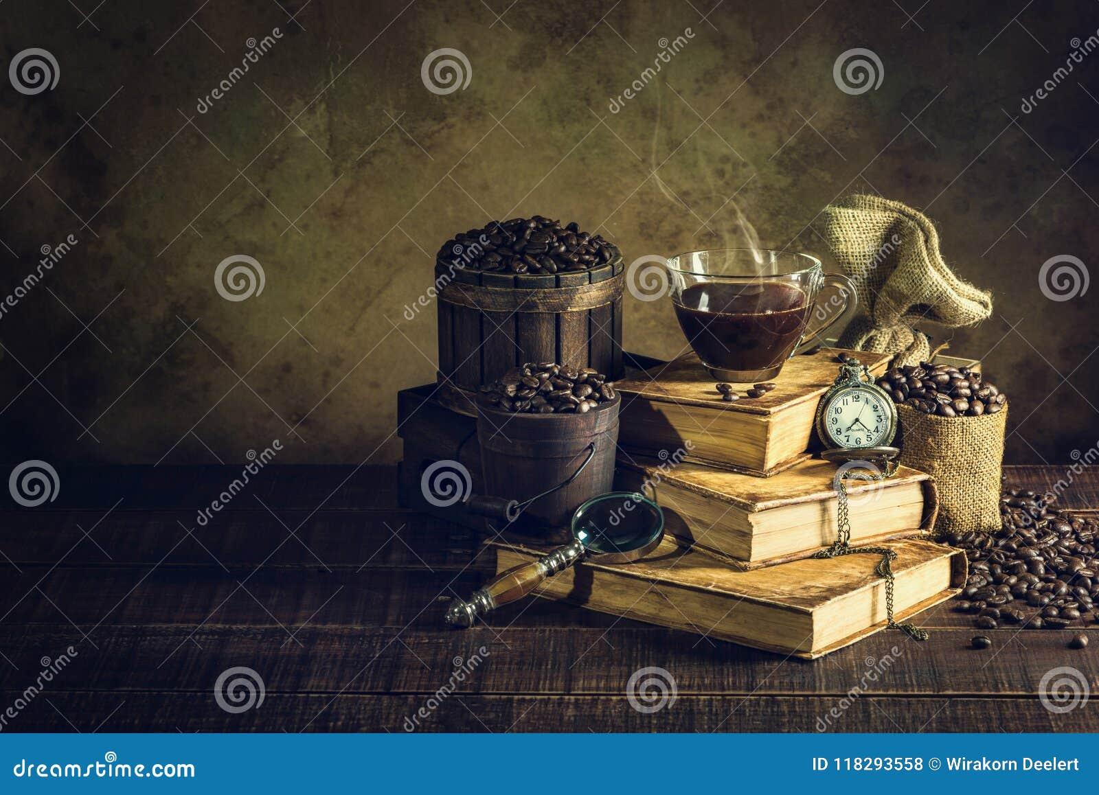 Koffie in kopglas op oude boeken en klokwijnoogst op oud hout