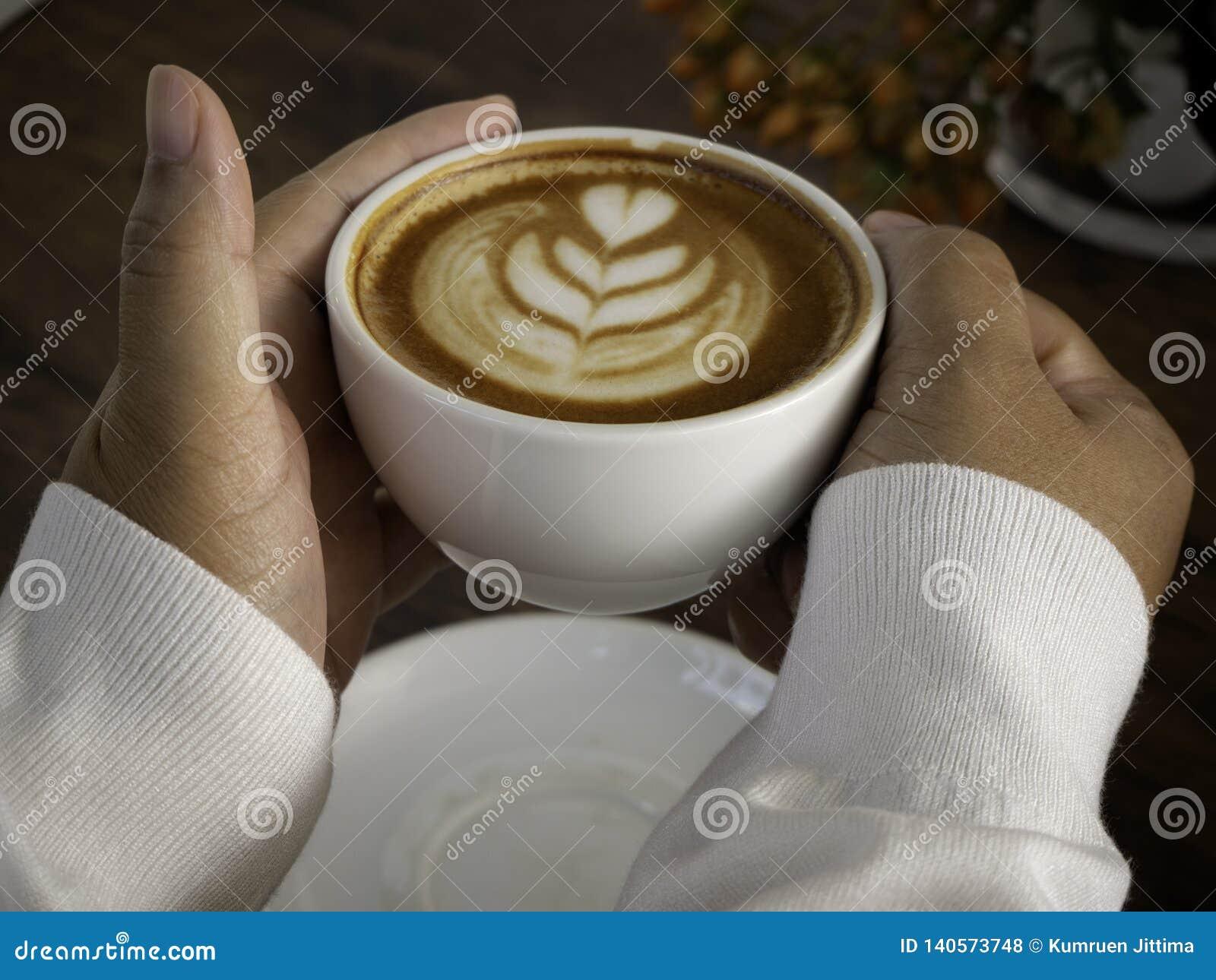 Koffie latte met mooie lattekunst op hand