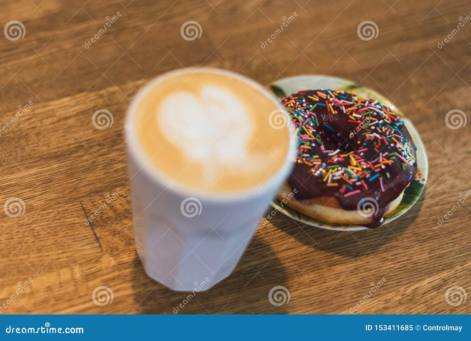 Koffie met een hart van melk wordt gemaakt en een doughnut op een houten lijst die Koffie met een getrokken hart en melk op een h