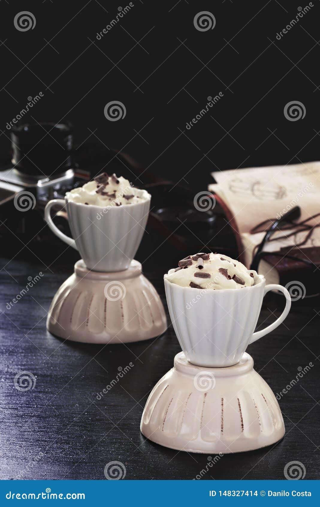 Koffie met zure room en chocolade op een houten achtergrond