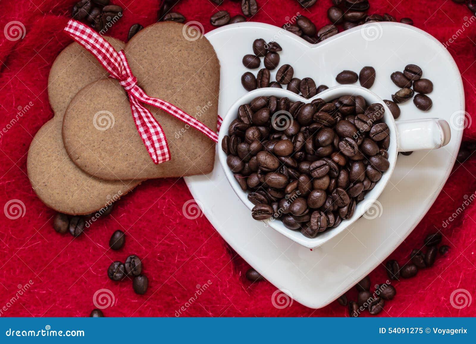 Koffiebonen in hart gevormd kop en dessert op rood