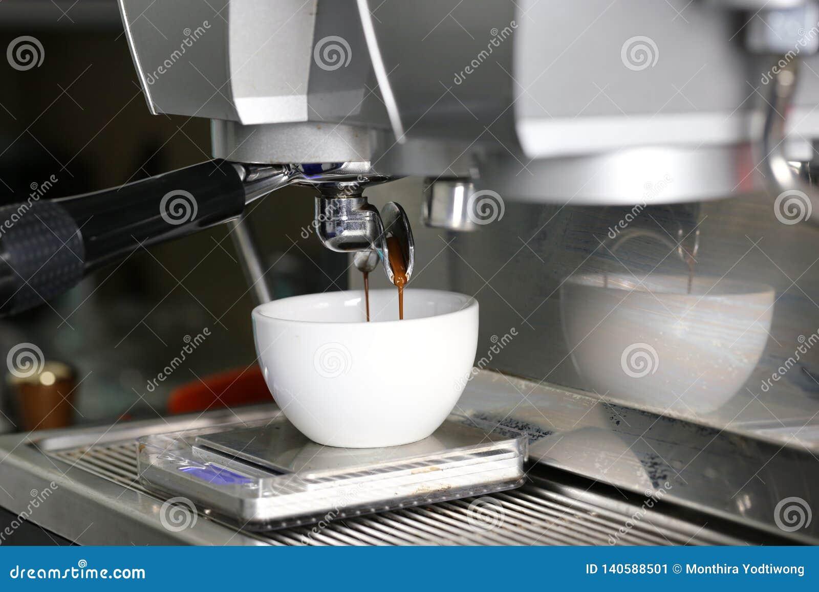 Koffieextractie het gieten in een kop van professionele koffiemachine met bar binnenlandse achtergrond