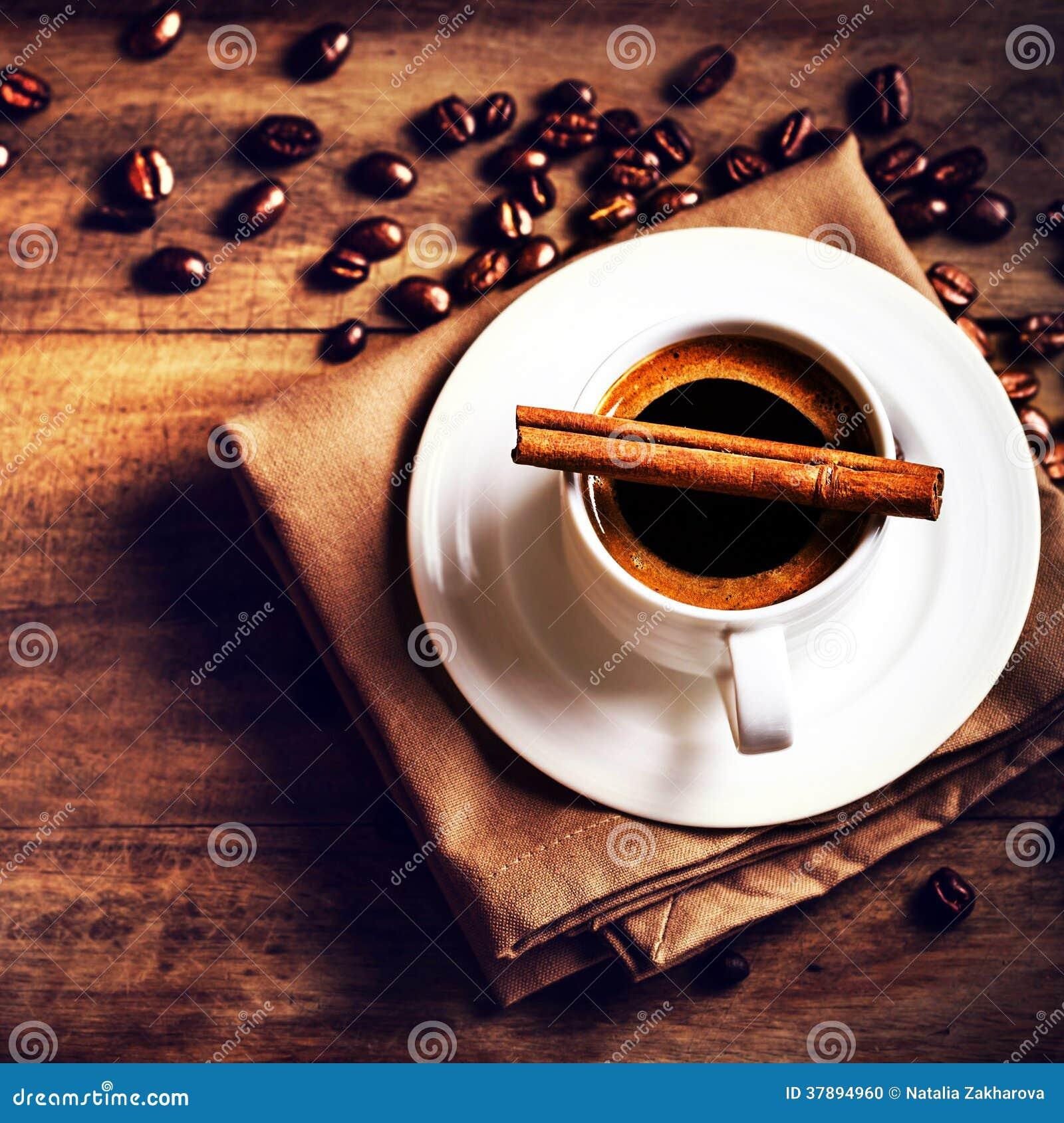 Koffiekop en geroosterde koffiebonen op houten bruine achtergrond