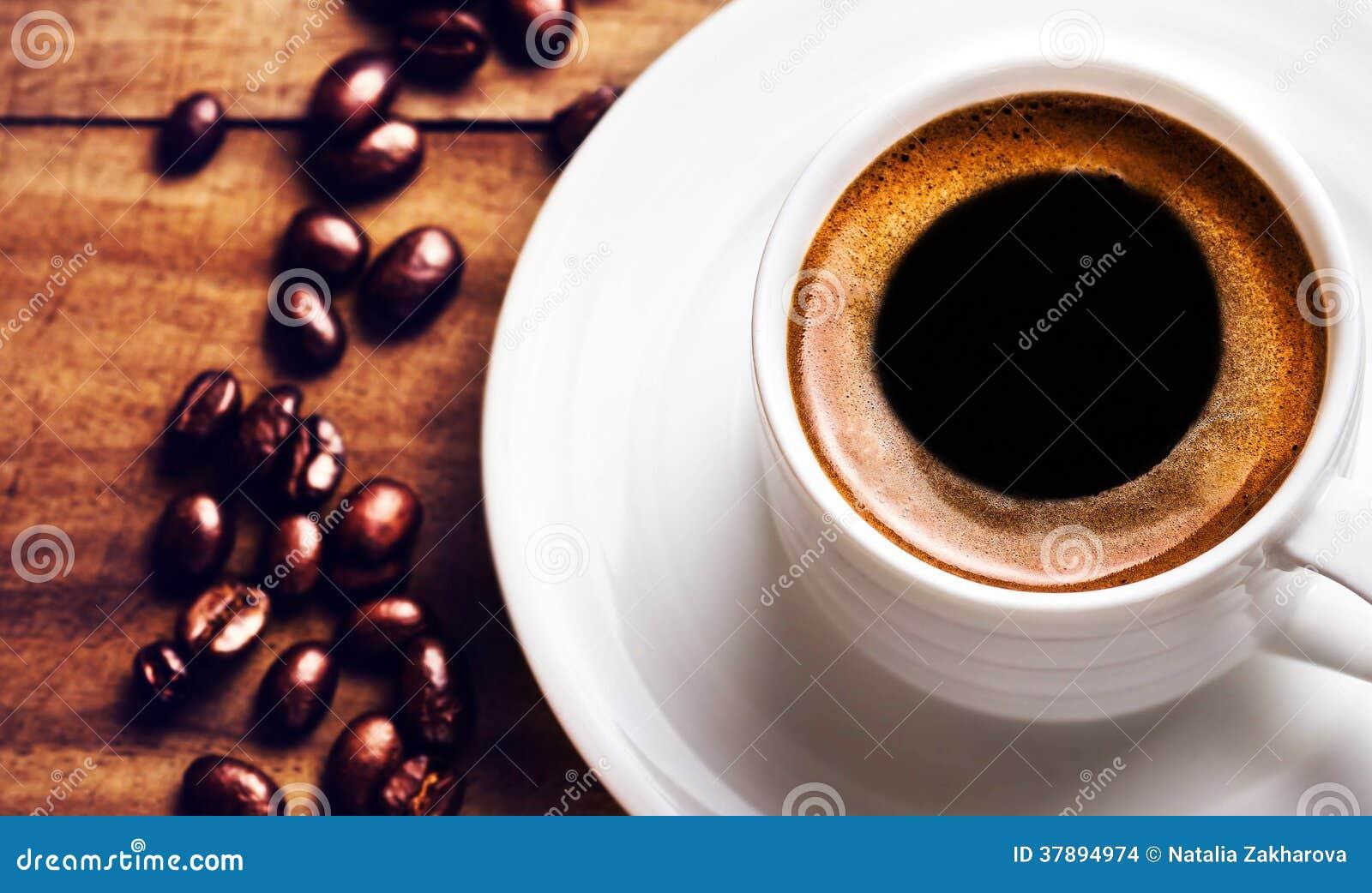Koffiekop met geroosterde koffiebonen op houten achtergrond, clos