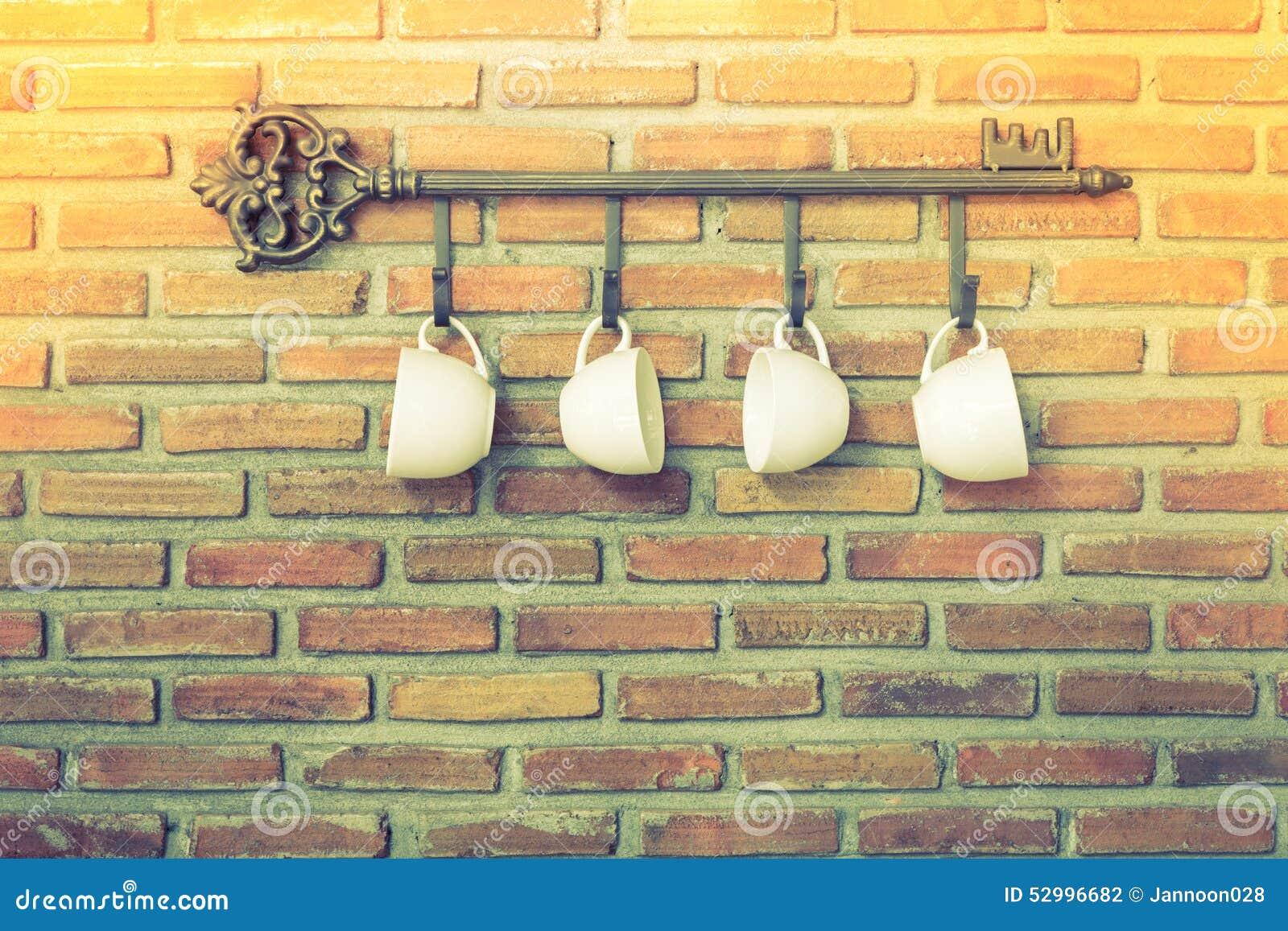 Koffiekoppen Die Op Haken Voor Bakstenen Muur Hangen Stock Foto