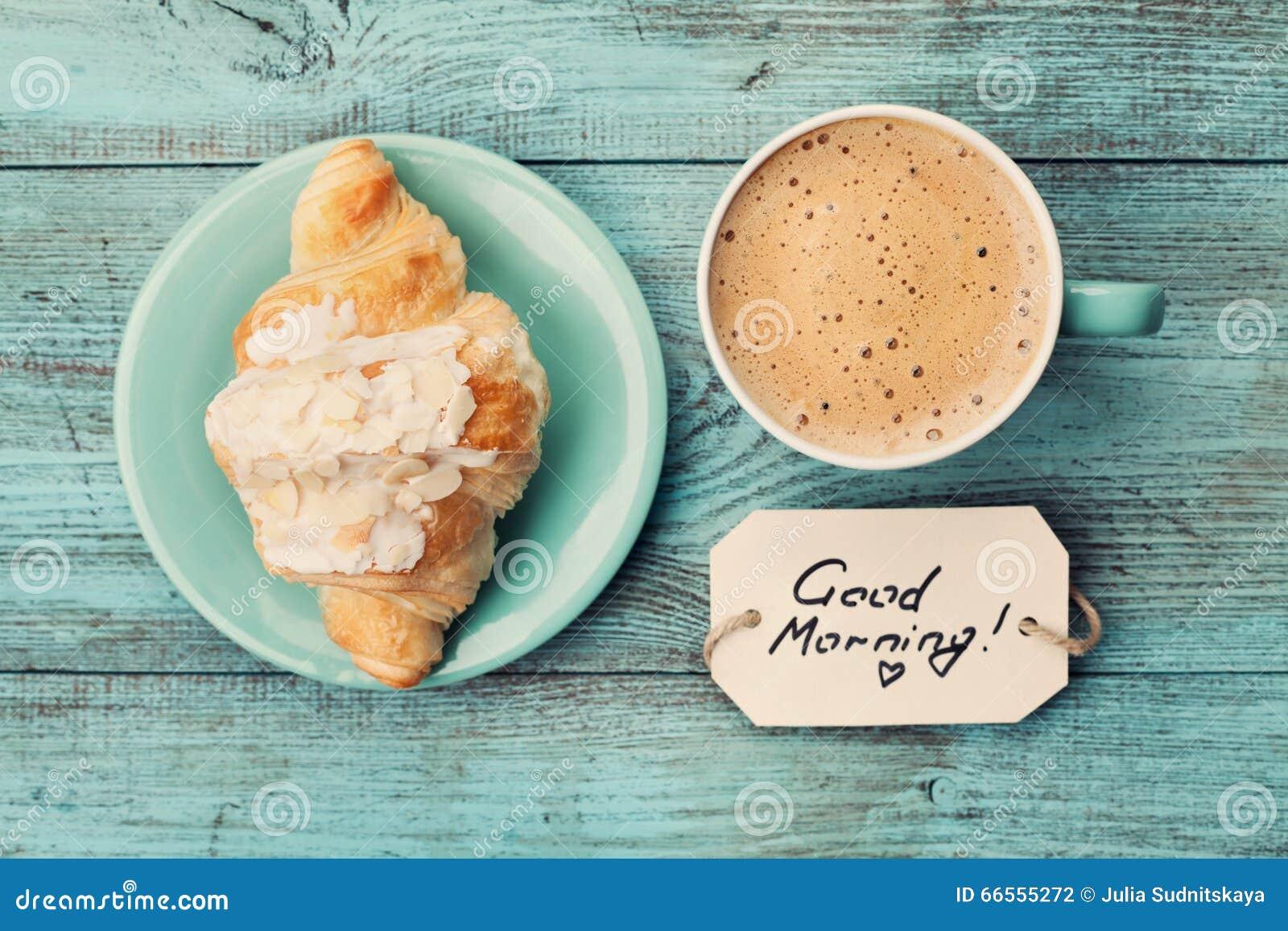 Koffiemok met hierboven, comfortabel en smakelijk croissant en nota sgoedemorgen op turkooise rustieke lijst van ontbijt