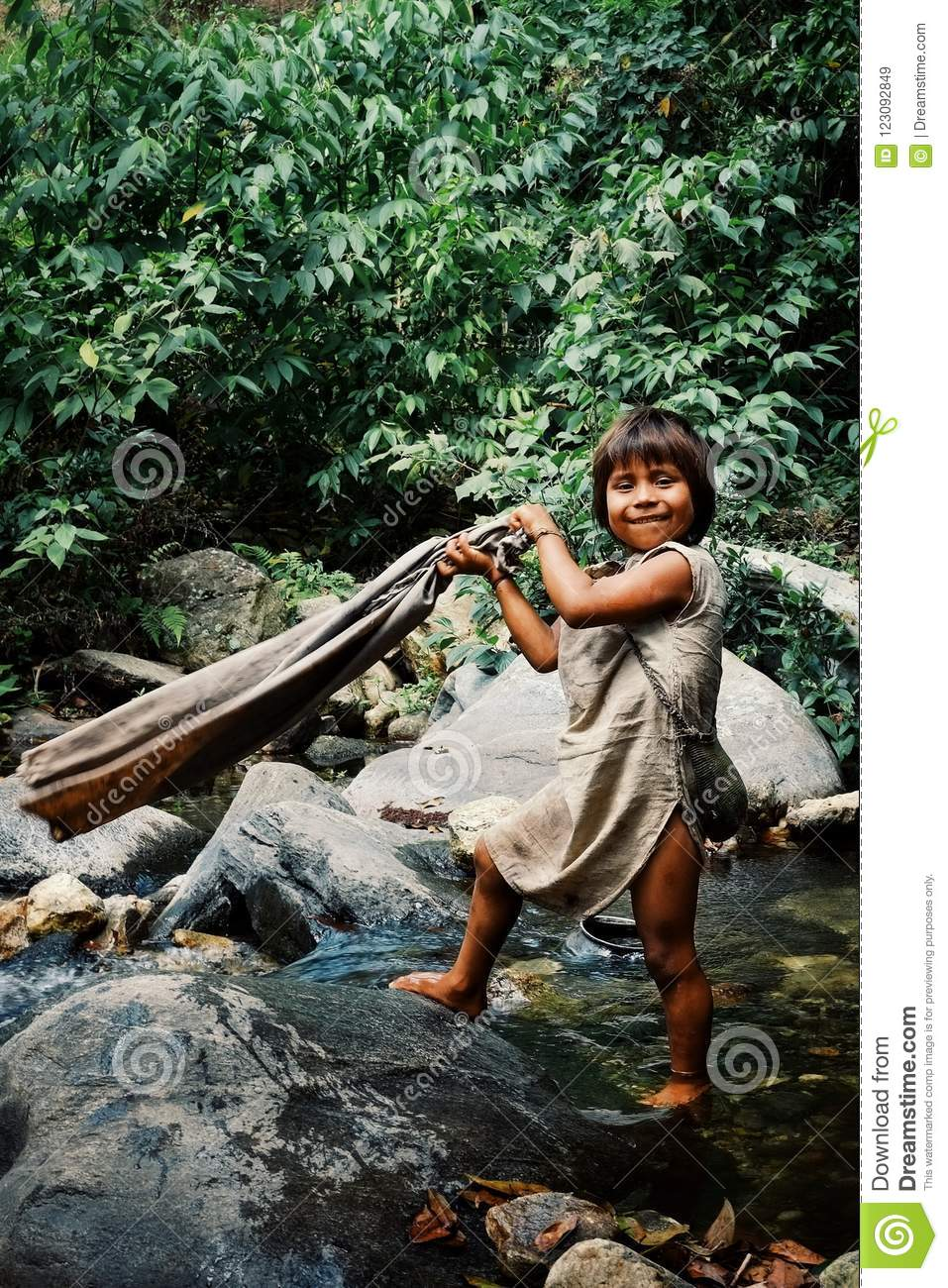 kogi tribal kid doing laundry in the nearby stream close to their home
