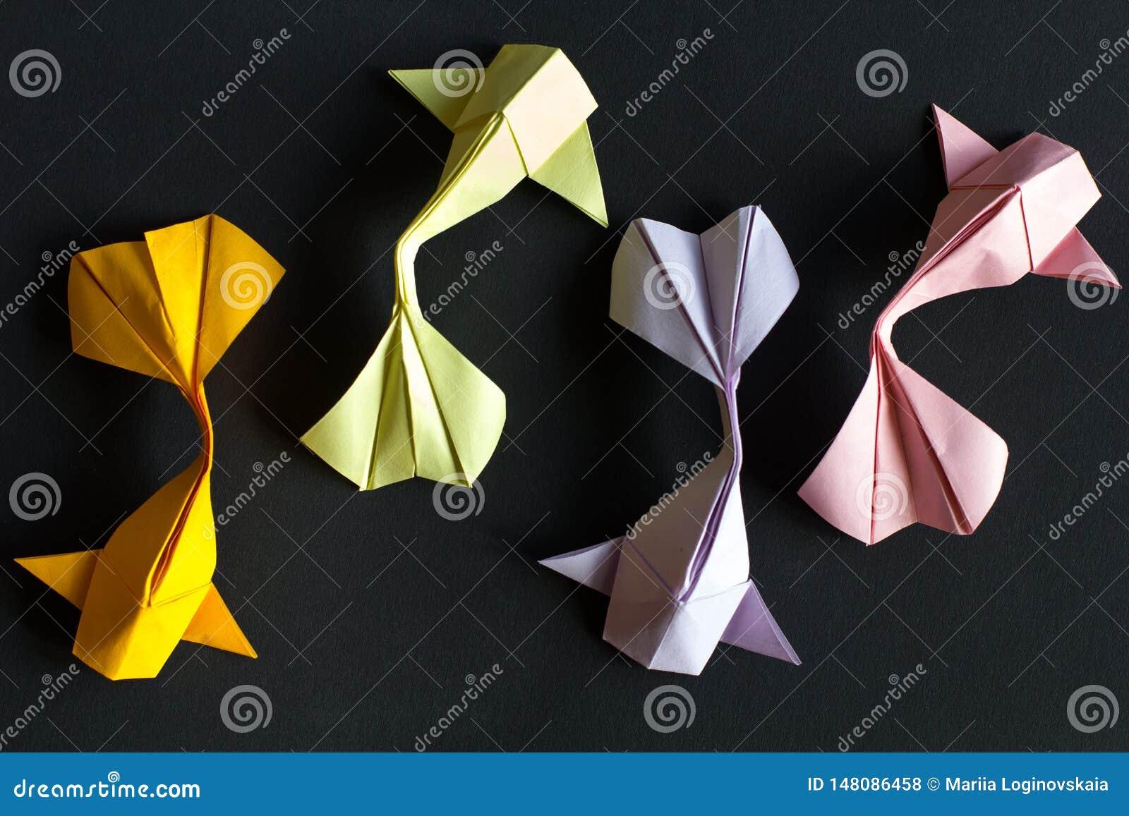 Koi feito a mão do ouro do origâmi do ofício de papel e rosa, peixes verdes, violetas da carpa no fundo preto Vista de cima de, t