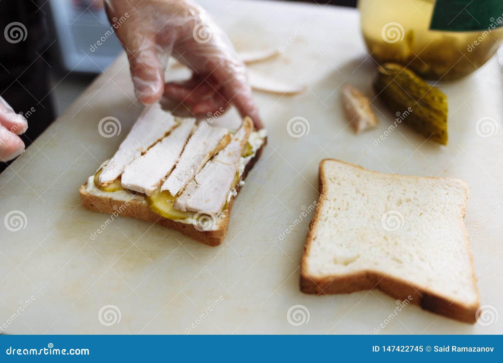 Kok die in polyethyleenhandschoenen een sandwich op een witte raad maken