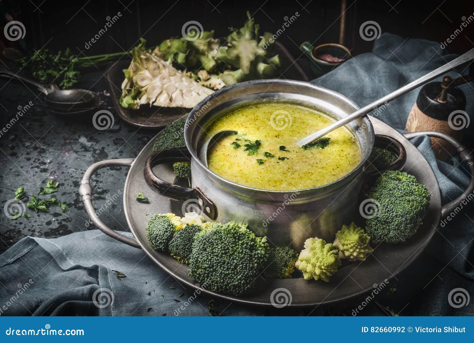 Kokende pot met groene romanesco en broccolisoep en gietlepel op donkere rustieke keukenlijst Gezonde voedsel en dieetvoeding