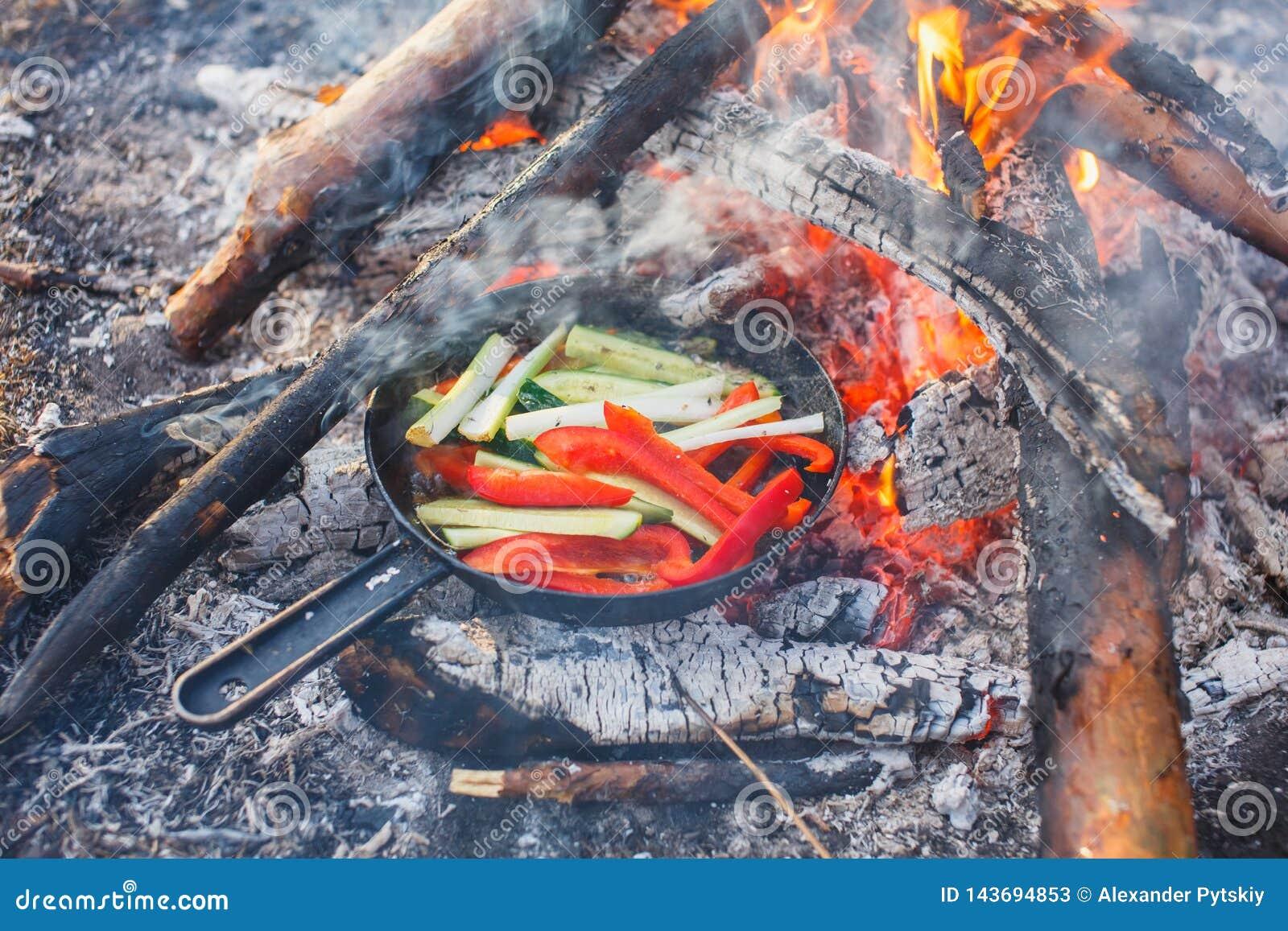 Kokende schotels van rode groene paprika s en komkommers in een pan op een brand