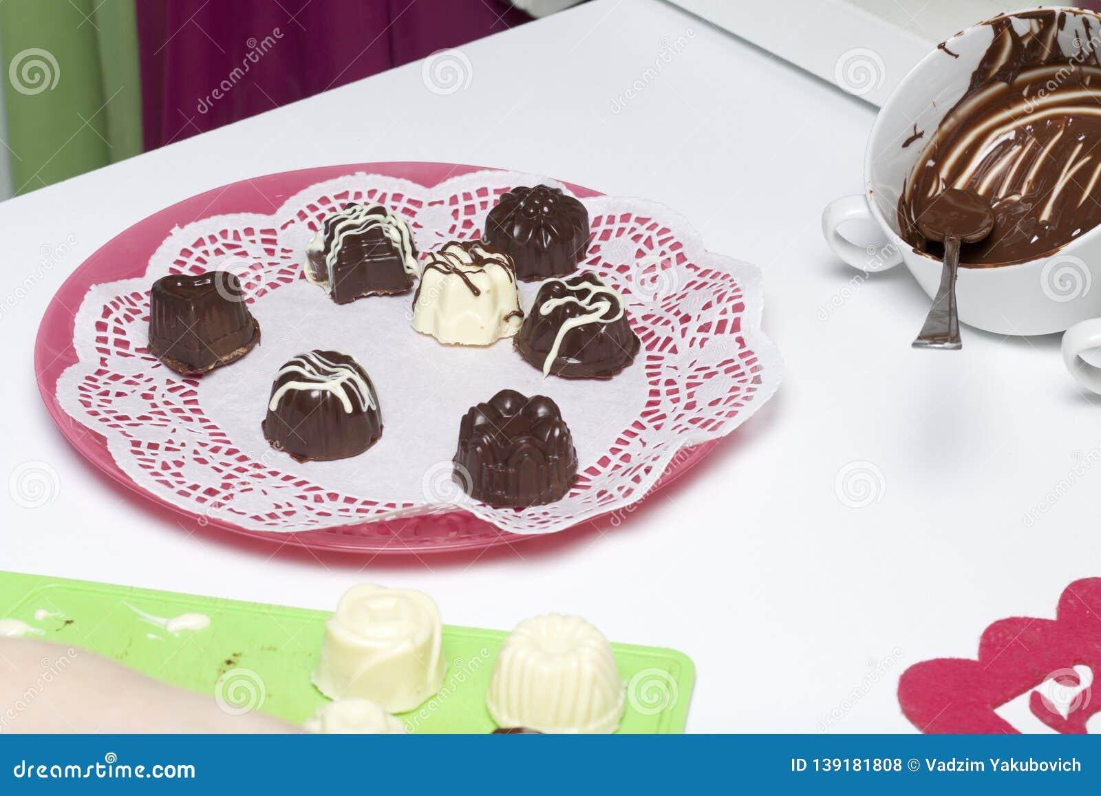 Kokende snoepjes met kokosnoot en condens In een glans van witte en zwarte chocolade