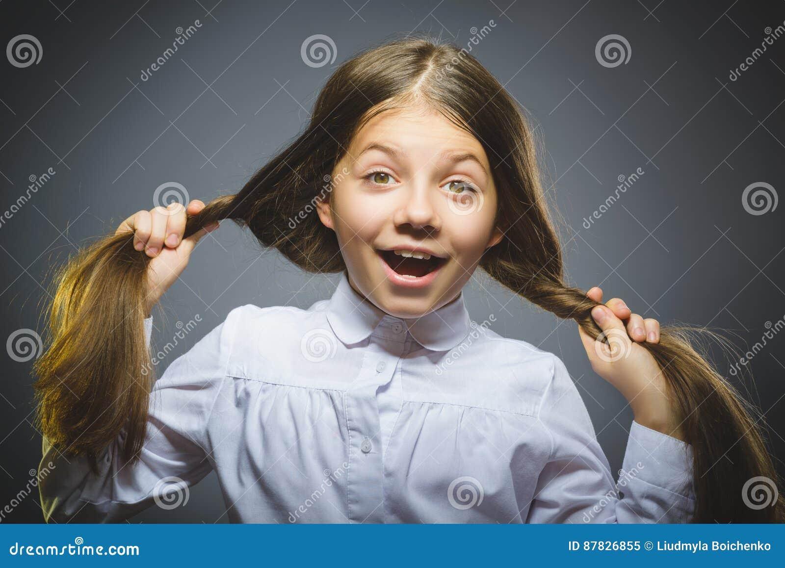 Koket meisje Het knappe de tiener van het close-upportret glimlachen geïsoleerd op grijs