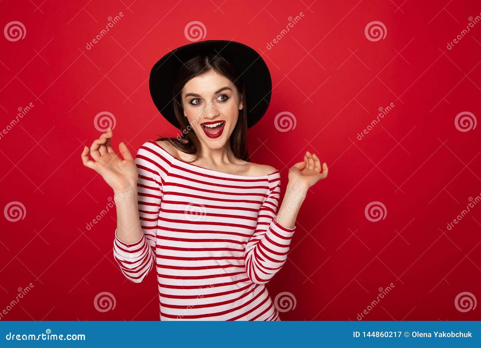Kokettes M?dchen in gestreifter Bluse und im schwarzen Hut