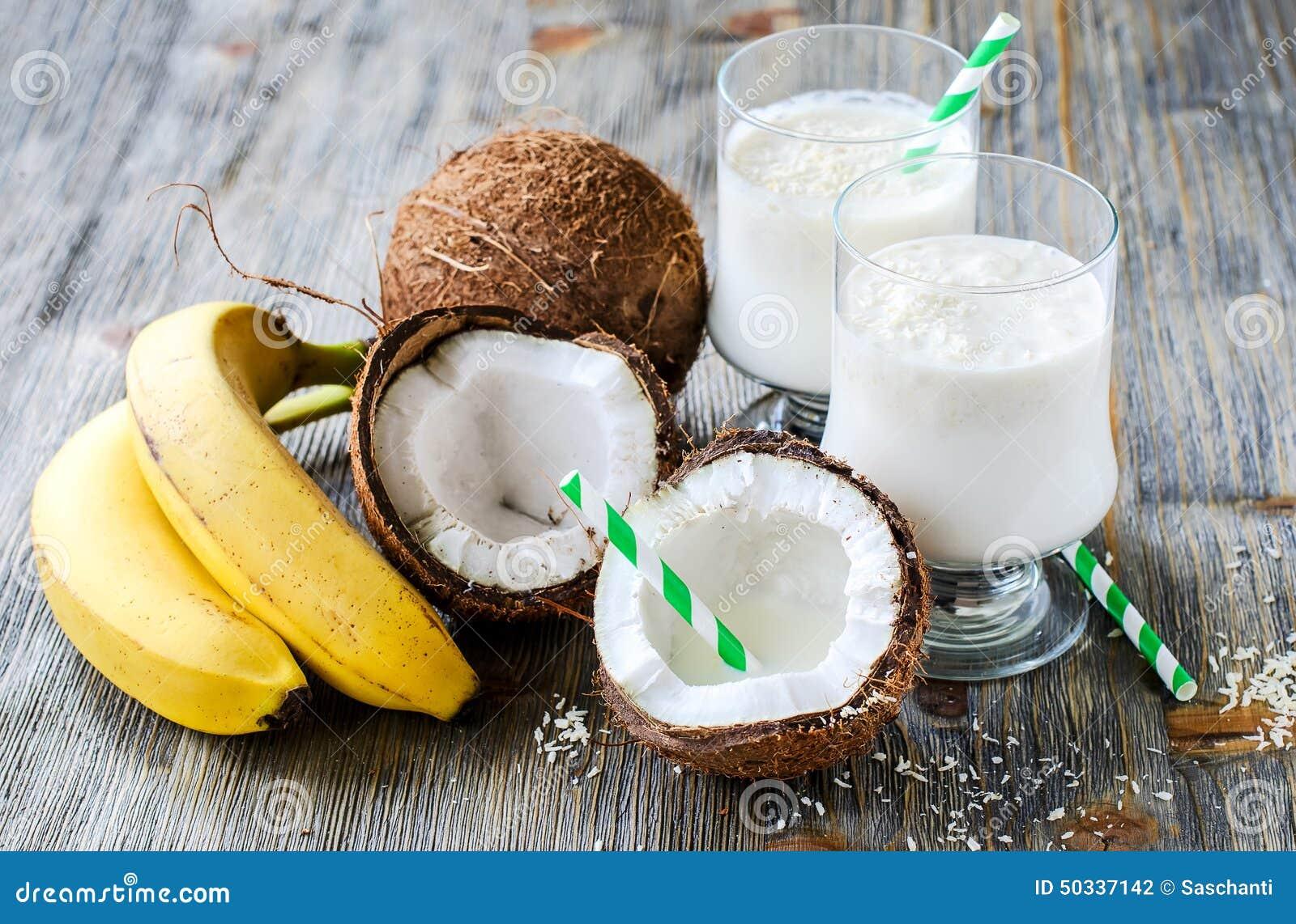 Kokosnöten mjölkar smoothiedrinken med bananer på träbakgrund