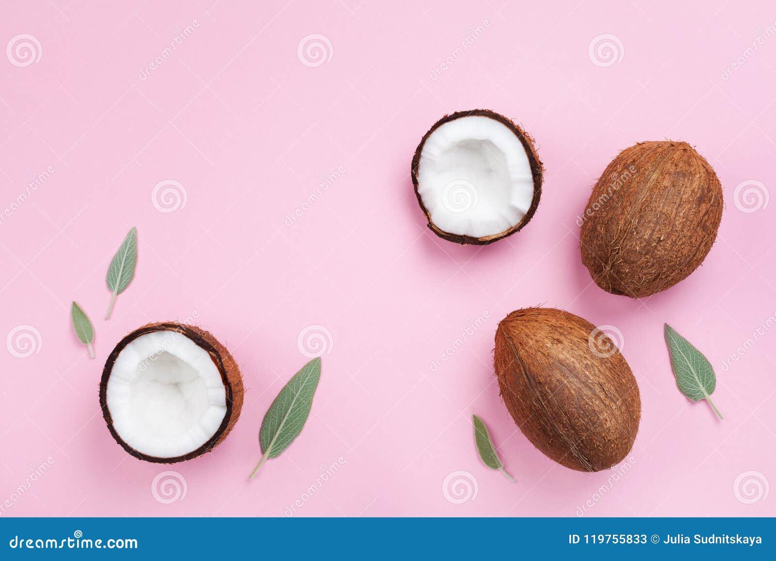 Kokosnussfrucht ganz und halb auf Draufsicht des rosa Pastellhintergrundes flache Lageart