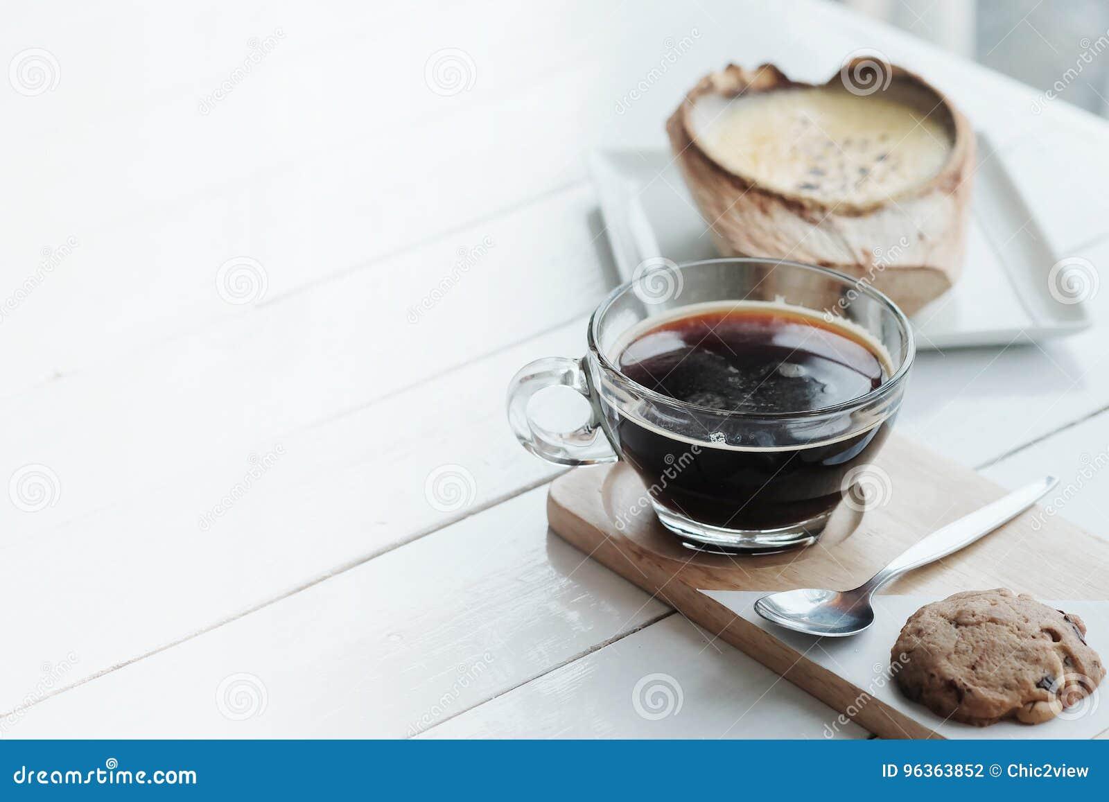 Kokosowy Creme Brulee jest cukierkowymi smakami i napojem z gorącego americano czarną kawą na białym drewnianym stołowym tle