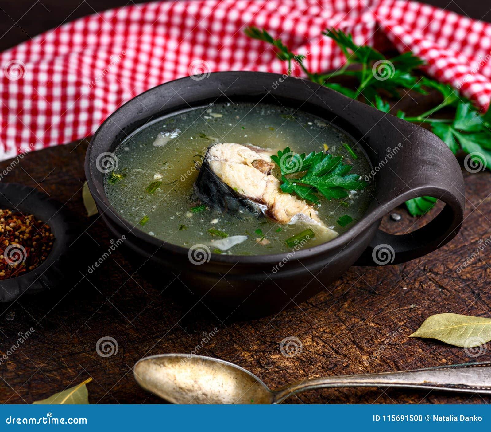 Kokt fisksoppa med makrillen i en brun leraplatta