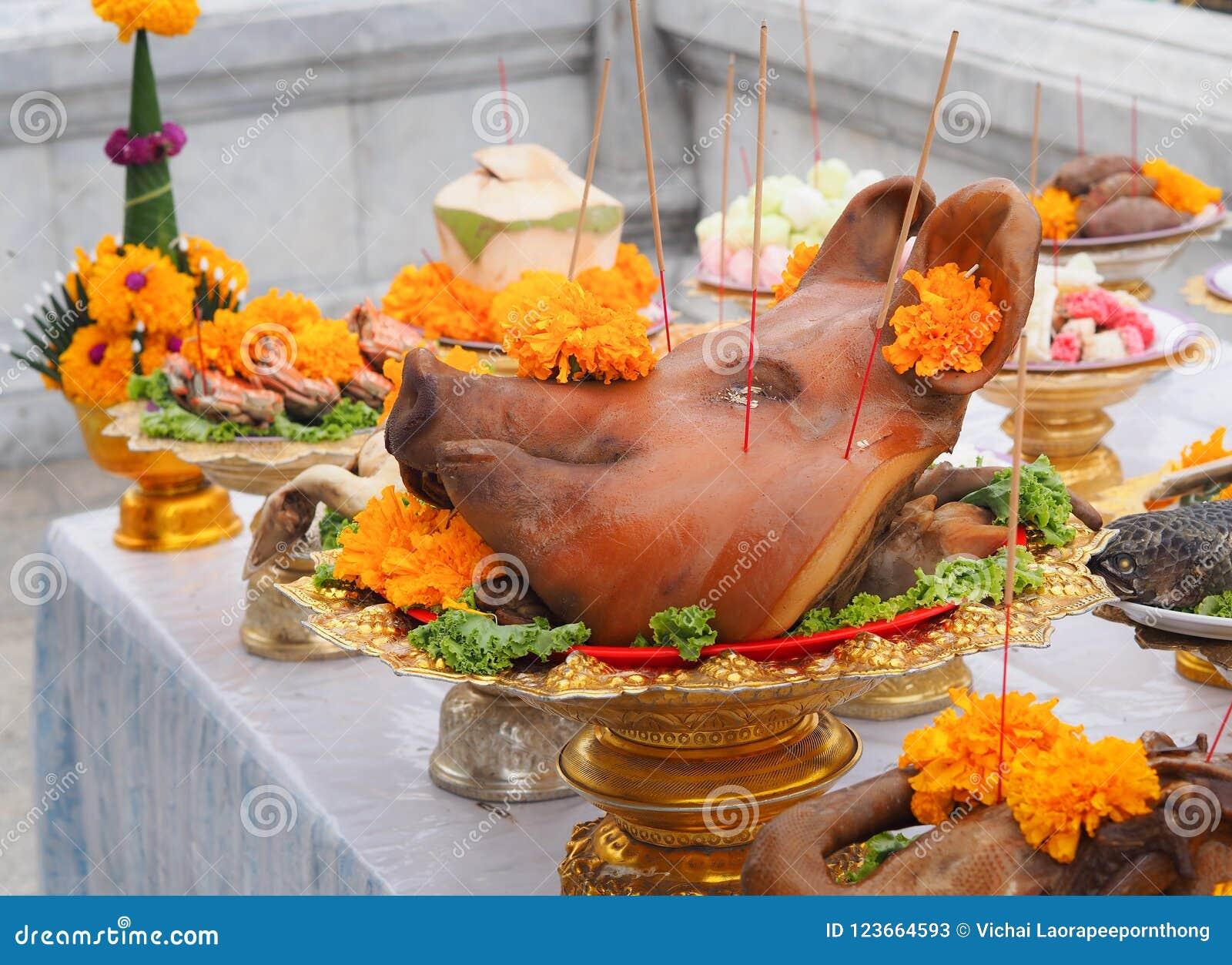 Kokta huvud för svin` s dekorerade med offer- erbjuda för blommor i dyrkan