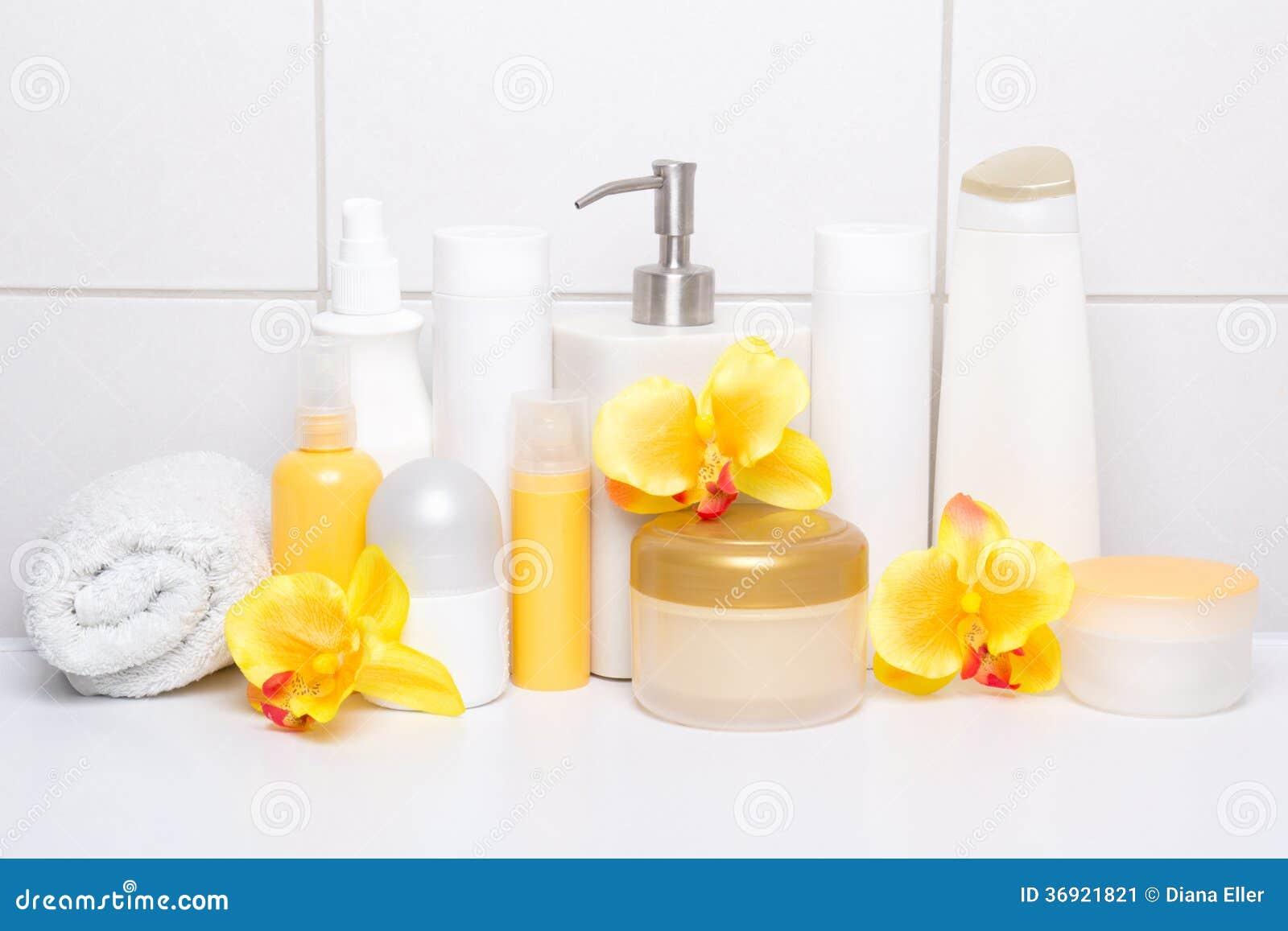 Kolekcja białe kosmetyk butelki z orchideami nad kafelkowy wal