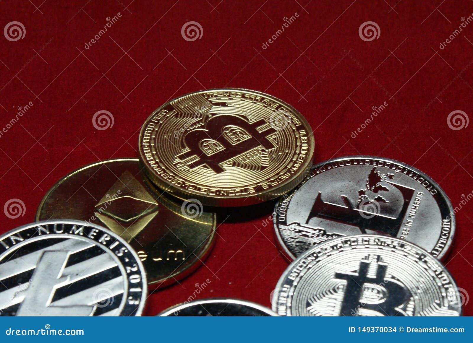 Kolekcja cryptocurrency monety na aksamitnym czerwonym tle