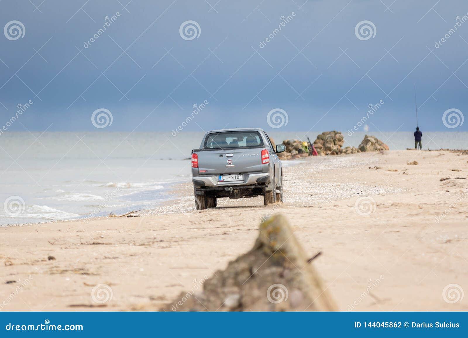 KOLKA, LETÓNIA - 26 DE OUTUBRO DE 2018: A defesa de Fiat pegara o caminhão que conduz na praia