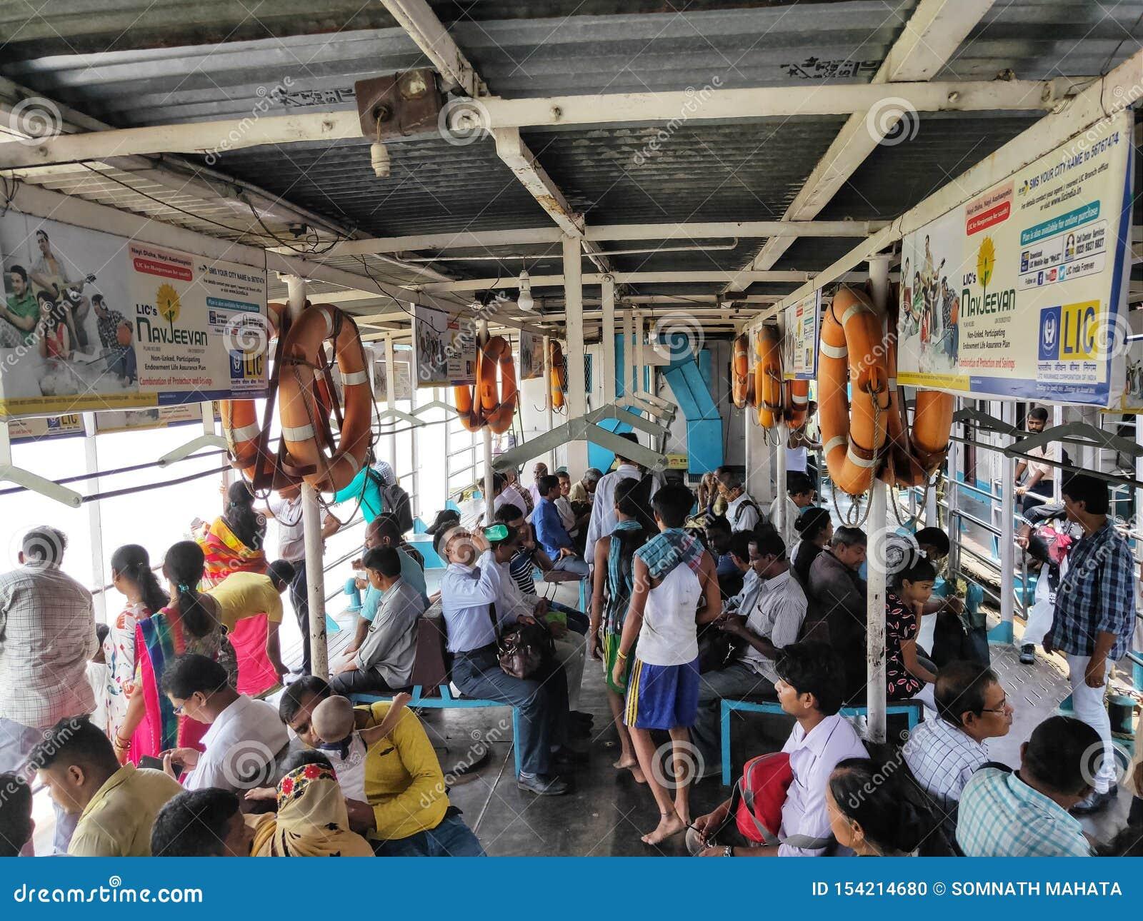 KOLKATA, INDIA - JULI 24, 2019: Mensen op de openbaar vervoerboot bij rivier Hoogly worden gezeten die Binnenvaart