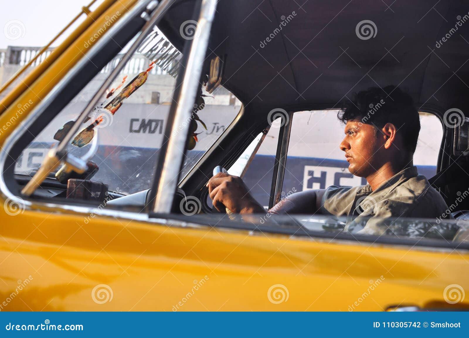 KOLKATA LA INDIA - ABRIL DE 2012: Hombre del taxista que conduce el coche en Kolkata, la India el 16 de abril de 2012