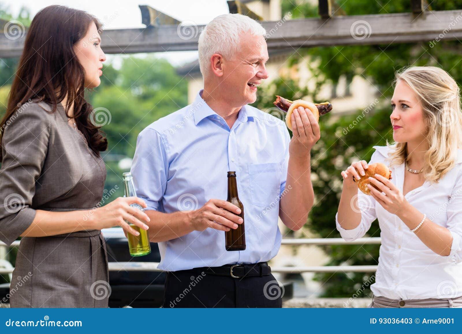 Kollegen Die Wurste Und Bier Nach Der Arbeit Essen Stockbild Bild