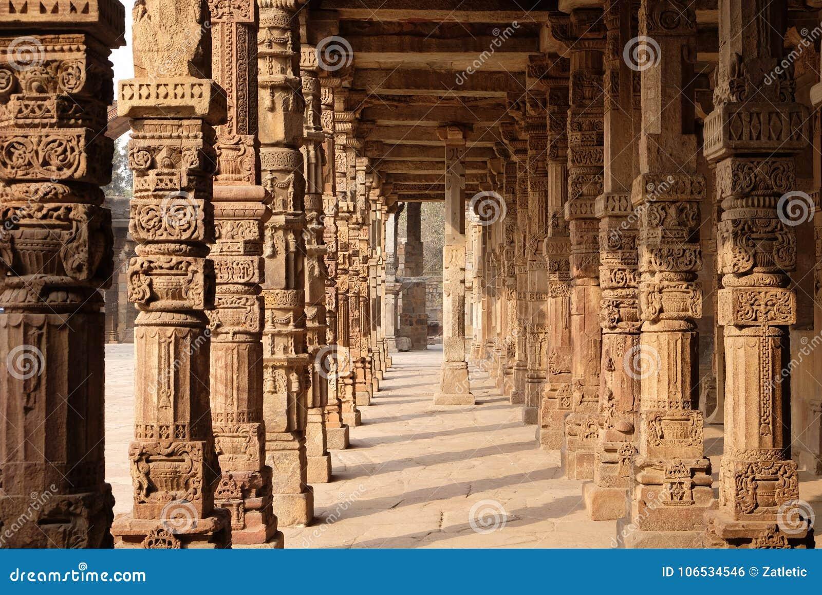 Kolommen met steen het snijden in binnenplaats van quwwat-Ul-Islam moskee, Qutab complexe Minar, Delhi