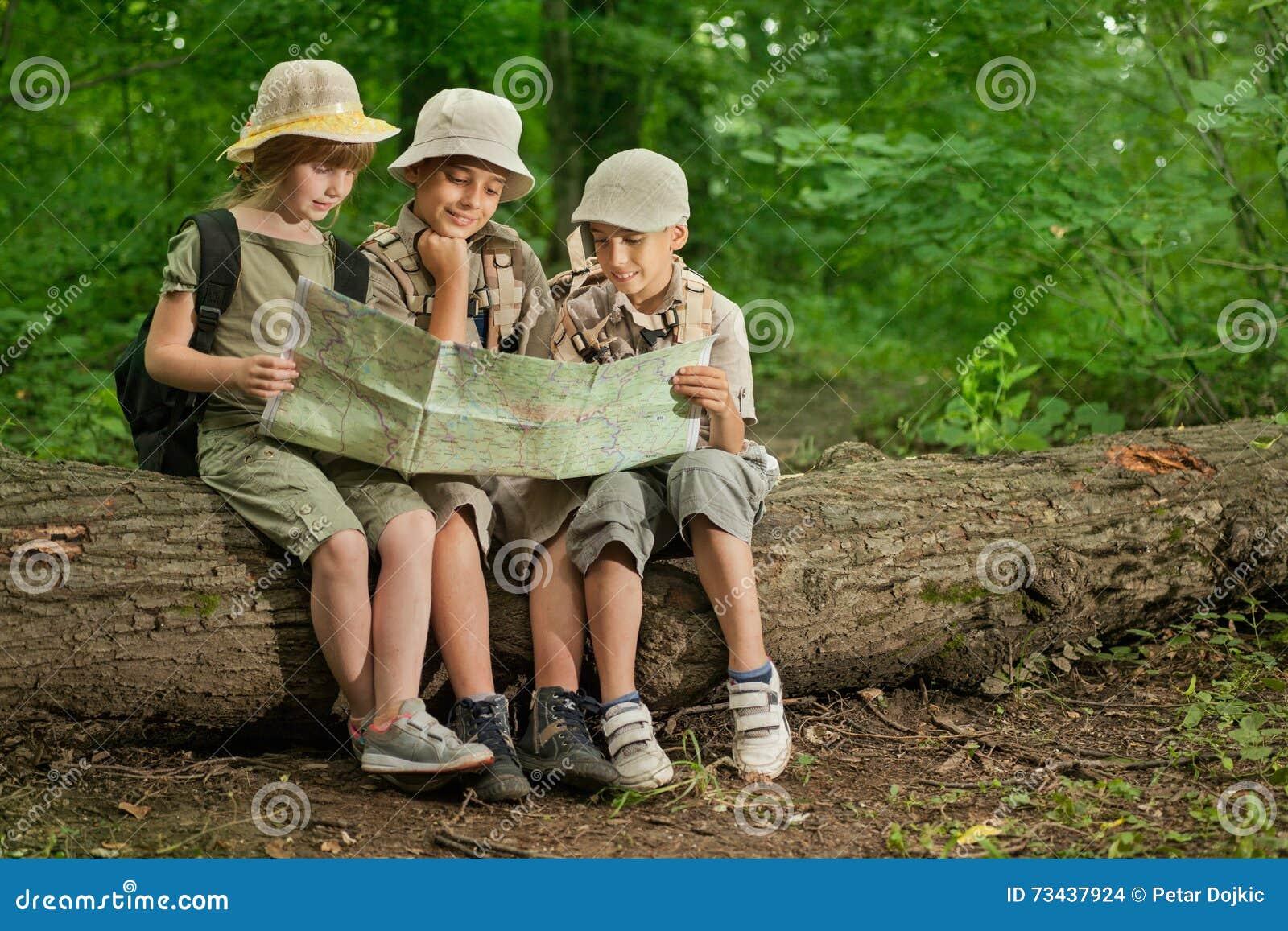 Kolonier spanar barn som campar och, läser översikten i skog