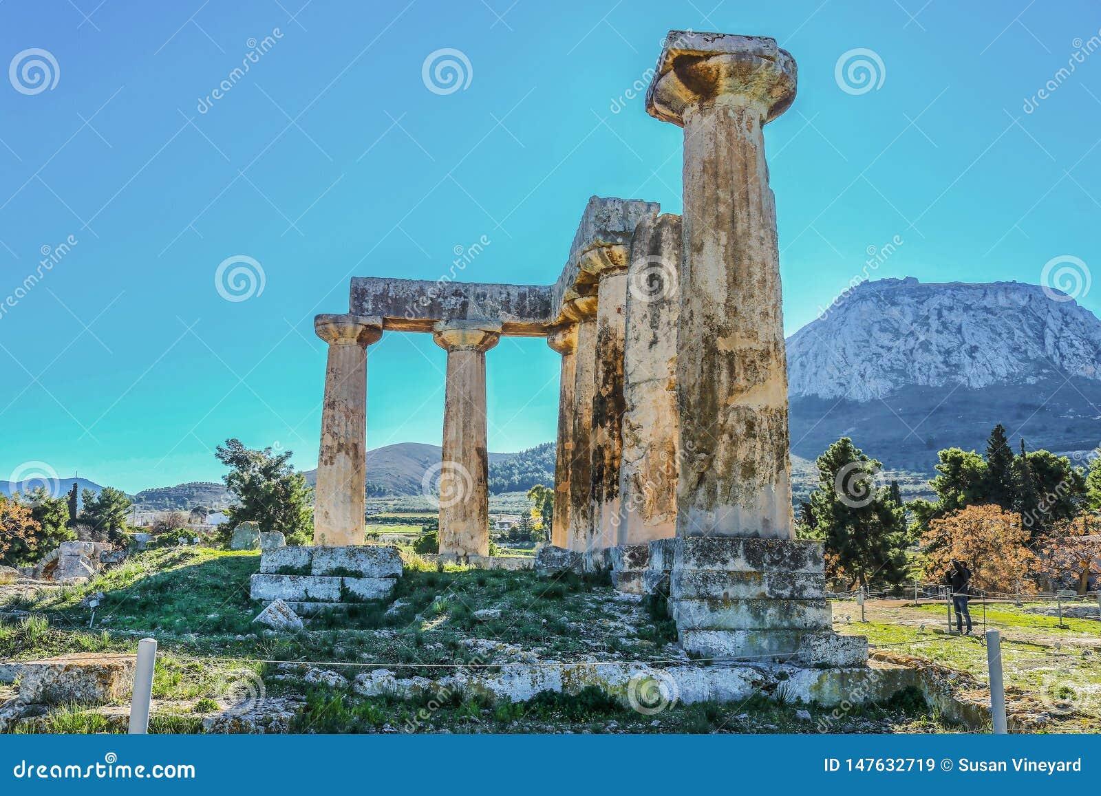 Kolonner fördärvar in av templet av Apollo med Acrocorinth akropolen av forntida Corinth - ett monolitiskt vaggar kontroll det fo