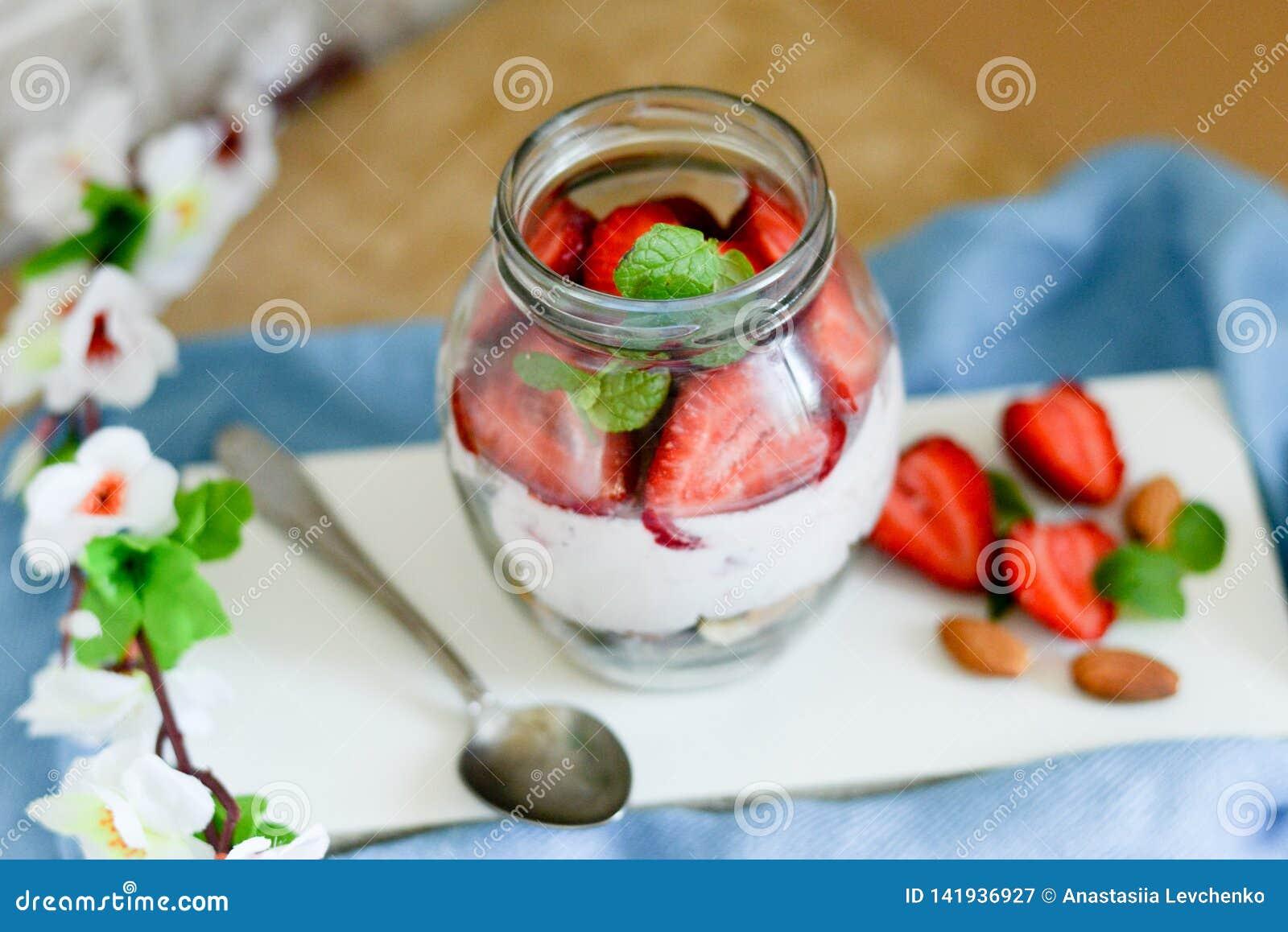 Kolorowa owocowa sałatka w słoju na białym i błękitnym nieociosanym drewnianym tle Odgórny widok Truskawkowy milkshake w słoju