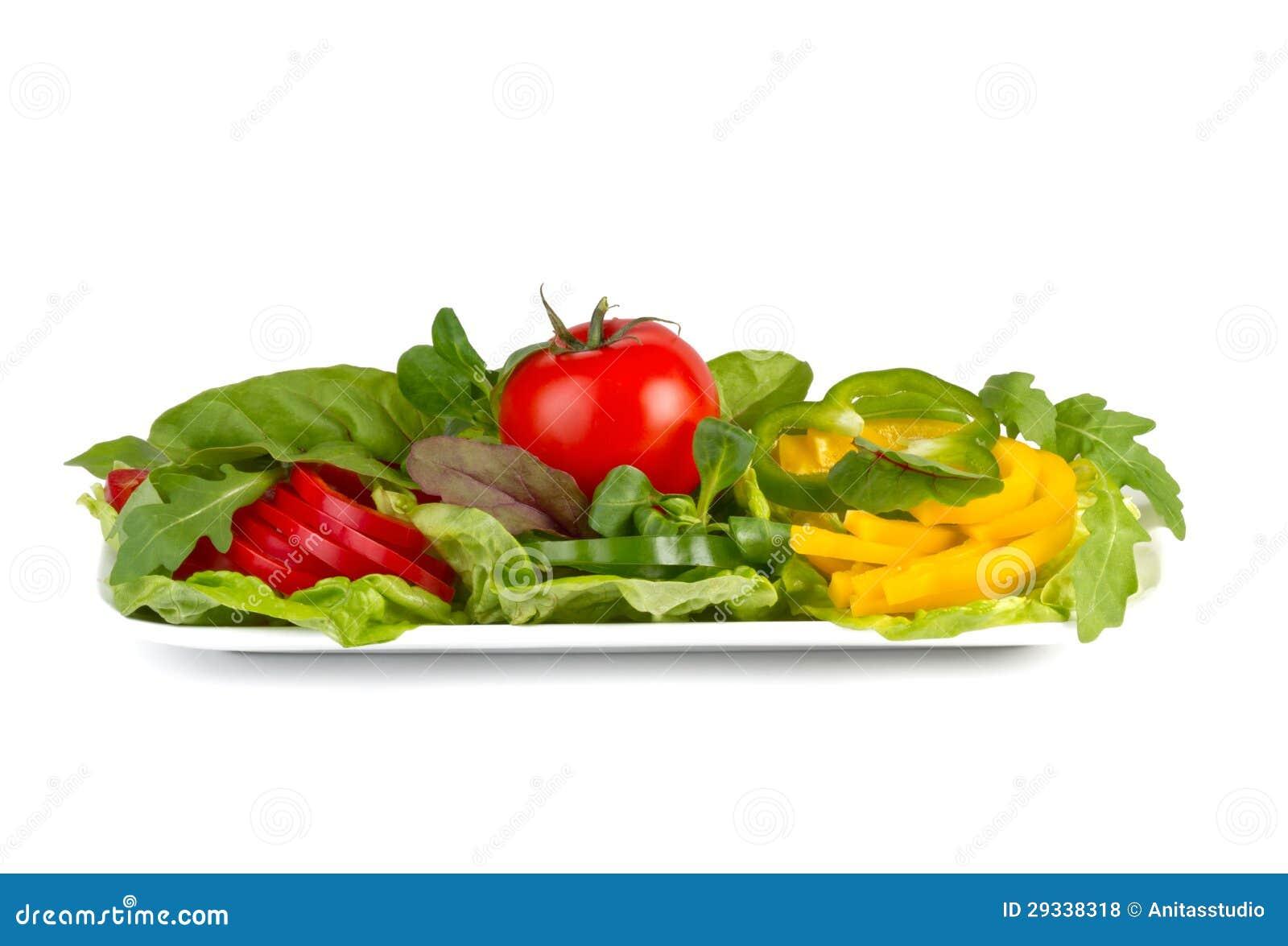 Kolorowi świezi warzywa na talerzu, odosobnionym na bielu