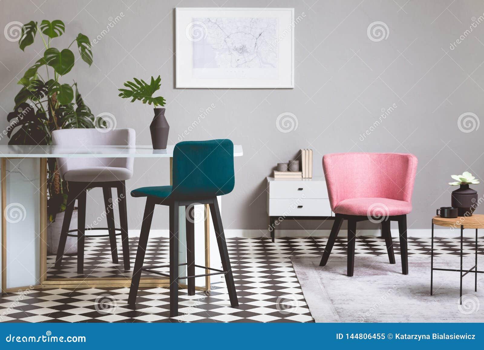 Kolorowi aksamitów krzesła w żywym pokoju z szkło stołem