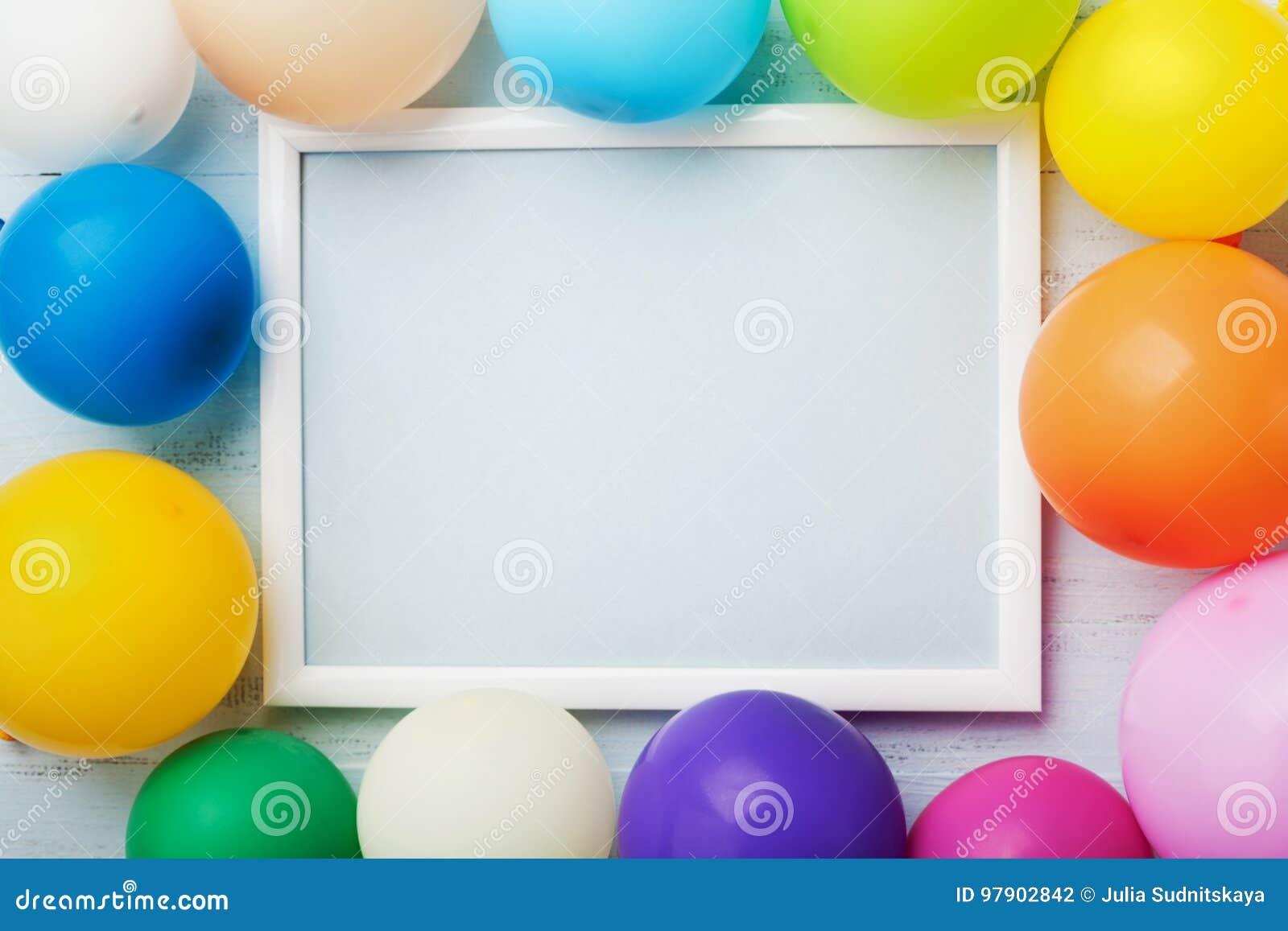 Kolorowi balony i biel rama na błękitnym drewnianym stołowym odgórnym widoku Mockup dla planistycznego urodziny lub przyjęcia mie