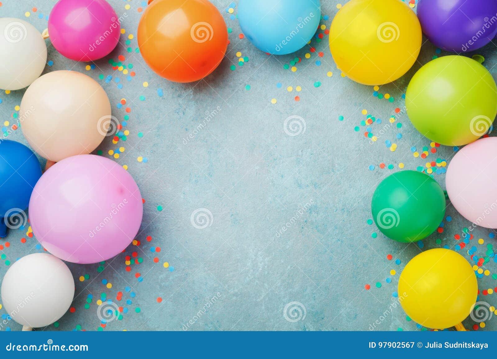 Kolorowi balony i confetti na błękitnym stołowym odgórnym widoku Świąteczny lub partyjny tło mieszkanie nieatutowy styl urodzinow