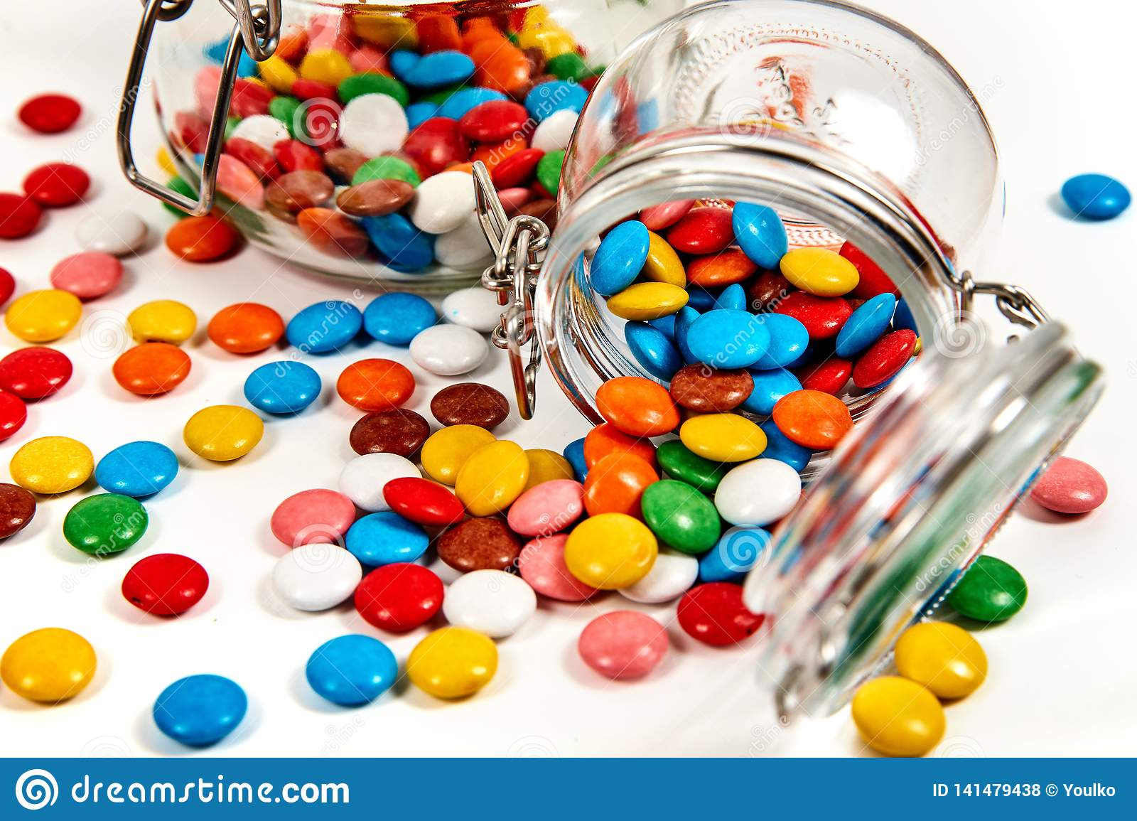 Kolorowi cukierki w szklanym słoju rozpraszali na bielu