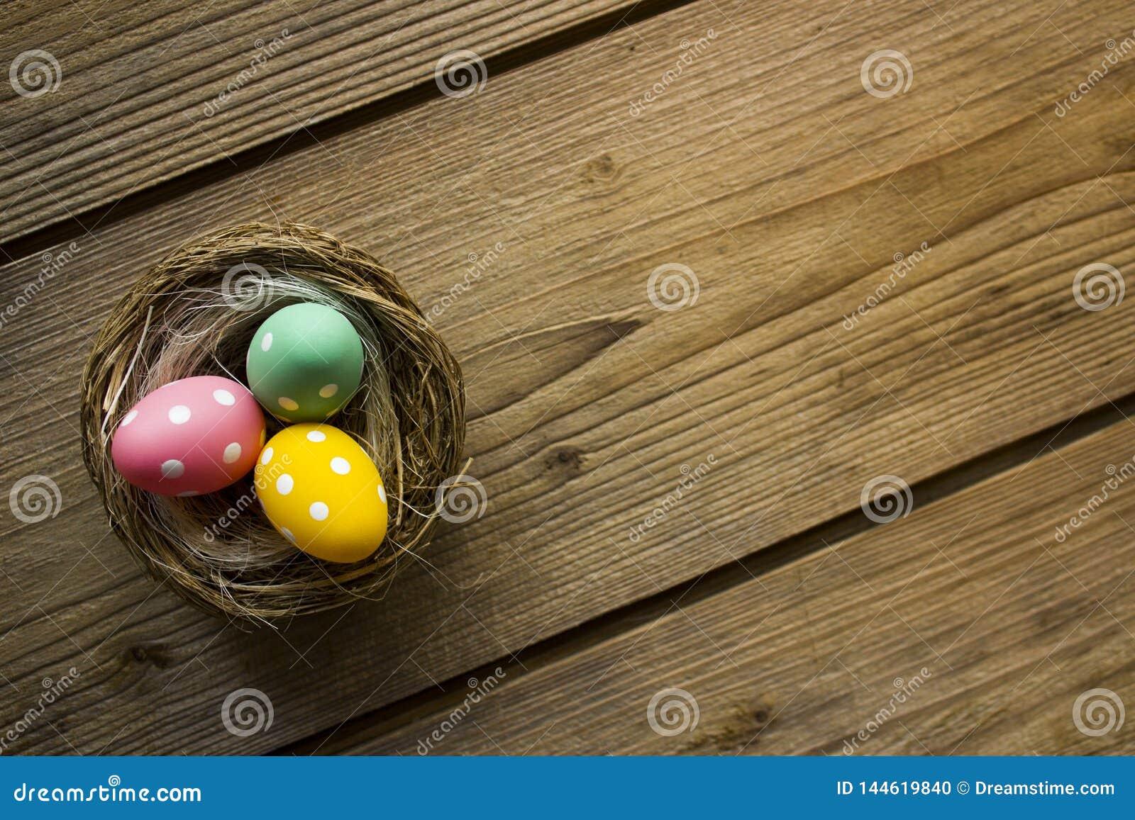 Kolorowi Easter jajka w gniazdeczku na drewnianym stole