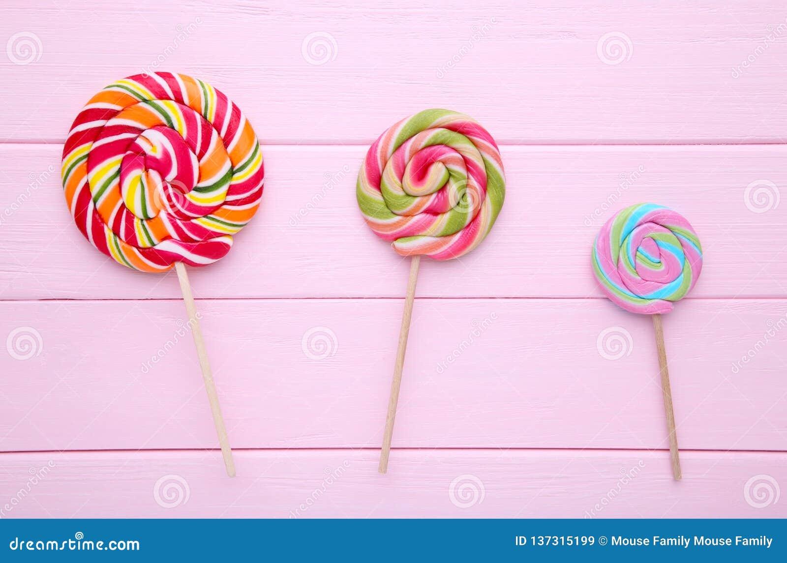 Kolorowi lizaki na różowym drewnianym tle, cukierki