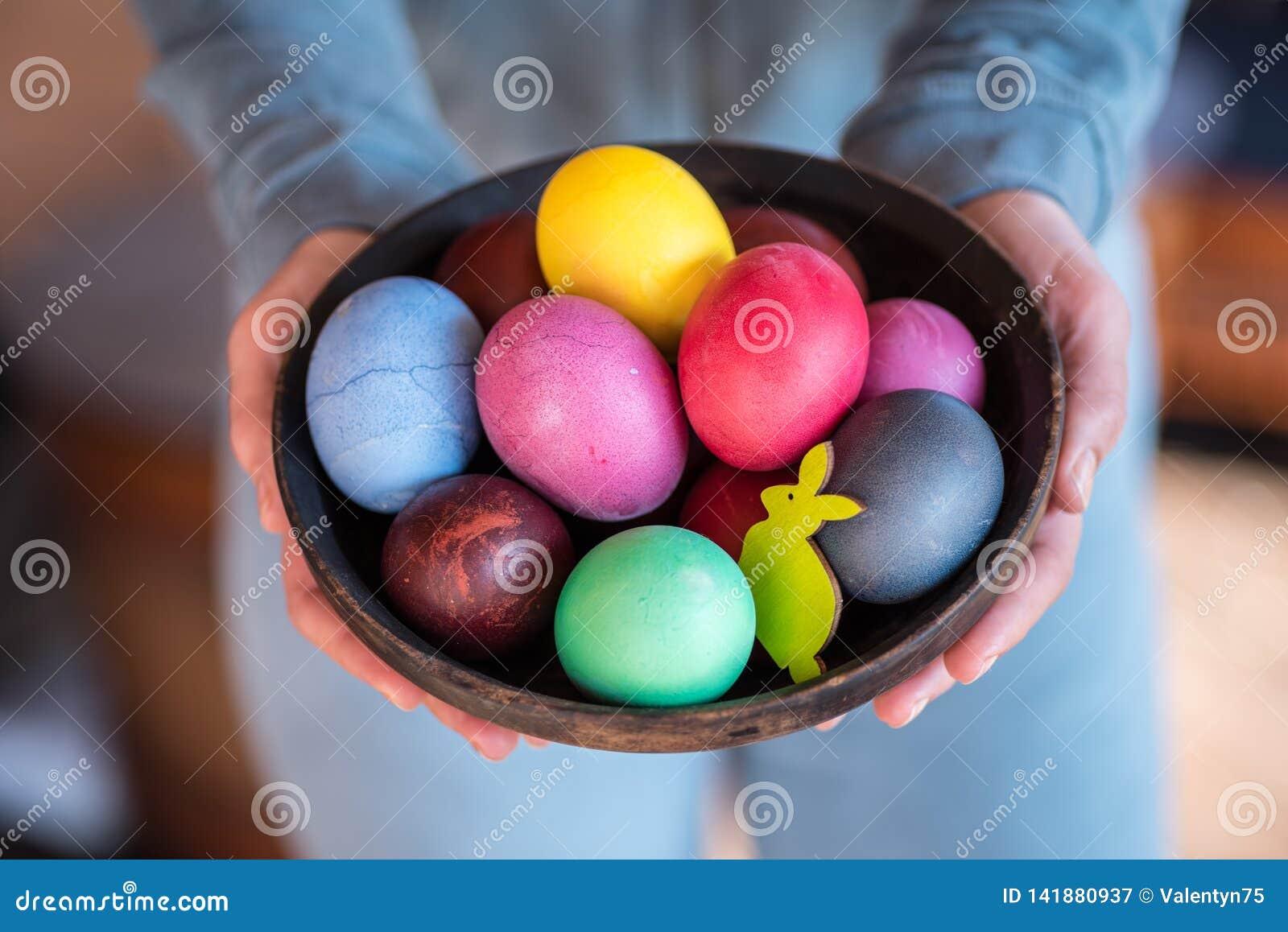 Kolorowi Wielkanocni jajka w pucharze w kobiet rękach