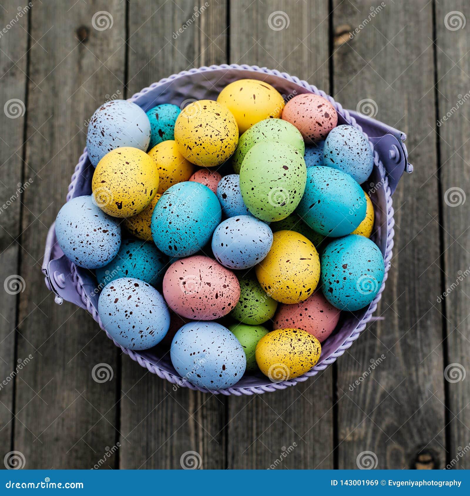 Kolorowi Wielkanocni jajka w wiadrze na drewnianym tle, wakacje karta