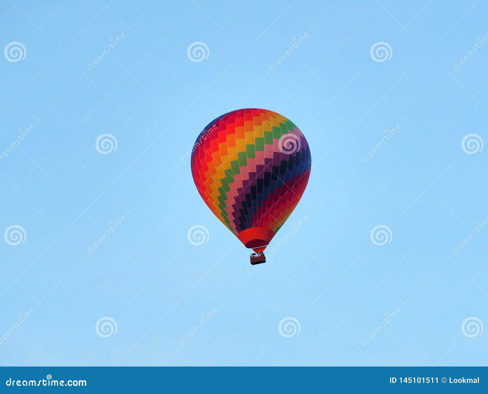 Kolorowy gorące powietrze balon przed jasnym niebieskim niebem